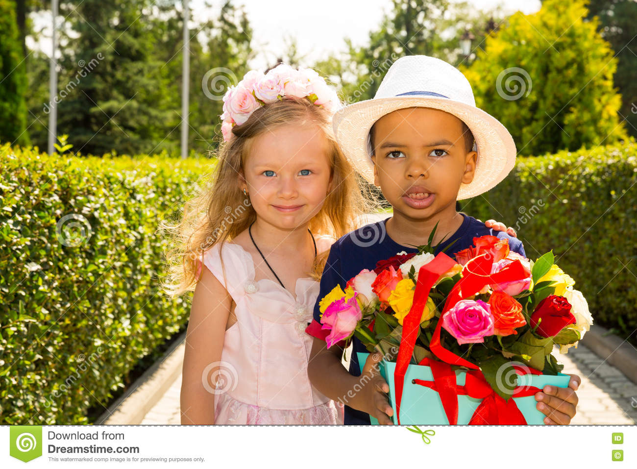 Black African American Boy Kid Gives Flowers To Girl Child On Birthday Little Adorable Children In Park Childhood And Love