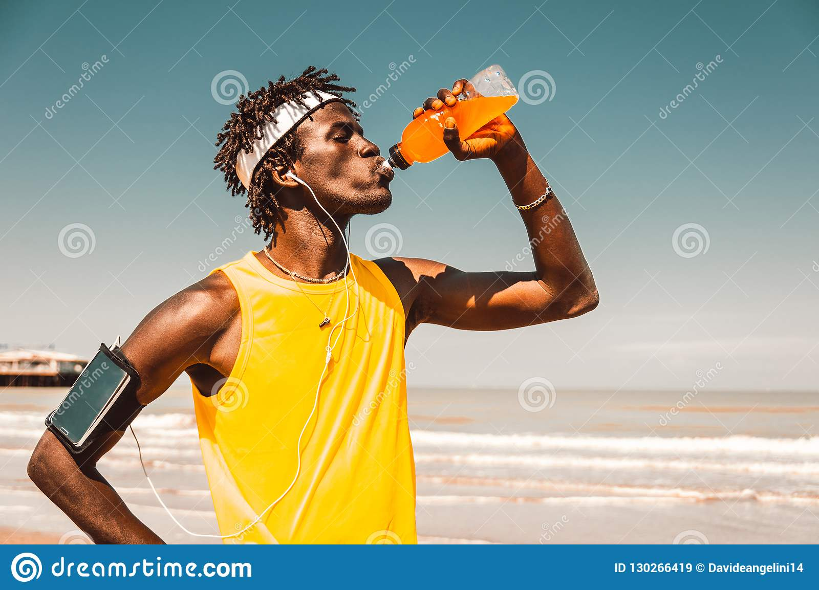 Running man at the beach drinking energy drink