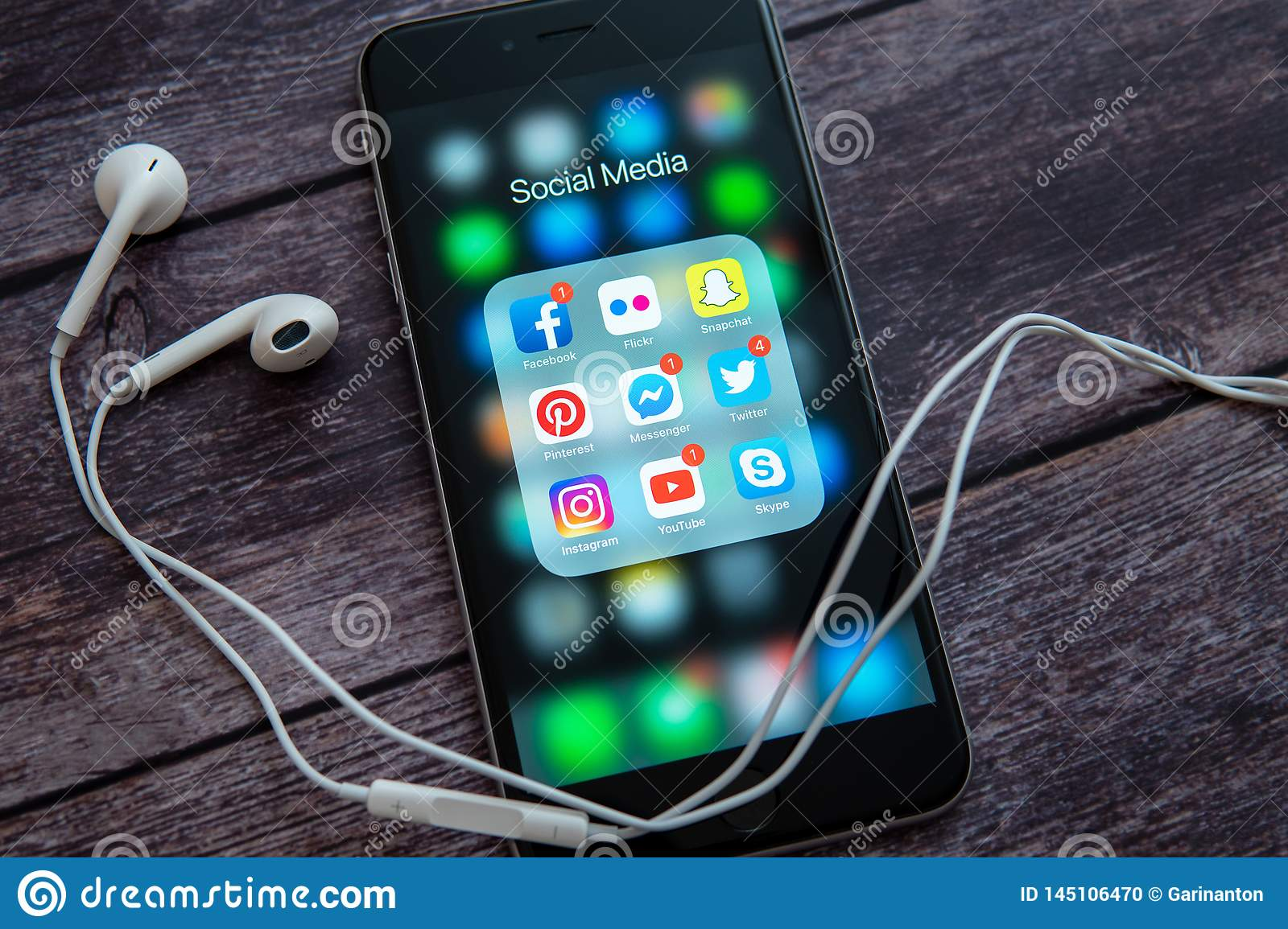 Black Apple iPhone with icons of social media and white headset