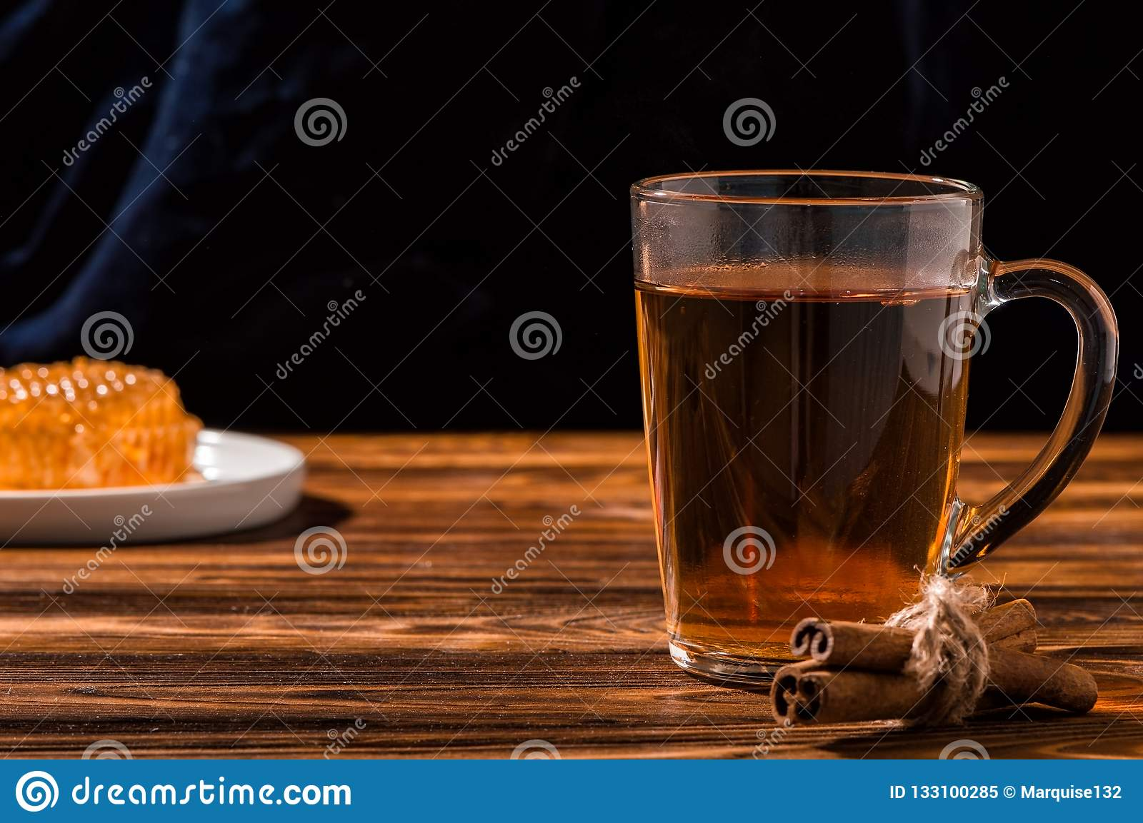 Black aromatic tea in a glass transparent cup. White plate with gold honey on a Rustic brown wooden table. Copy space