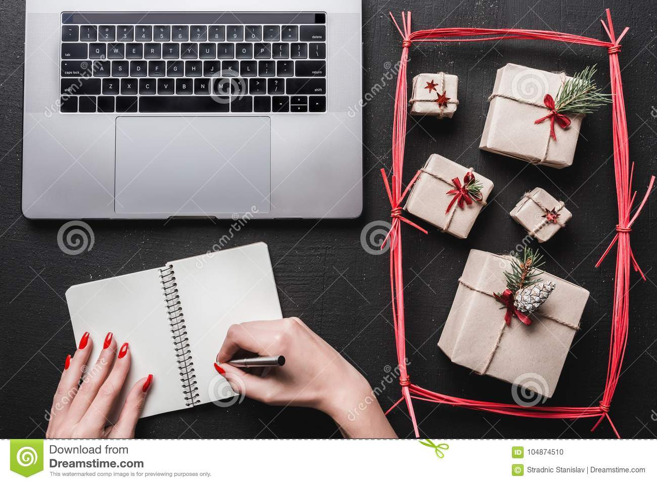 On black background, many gifts and computer. On a book, a lady`s hands want to write.