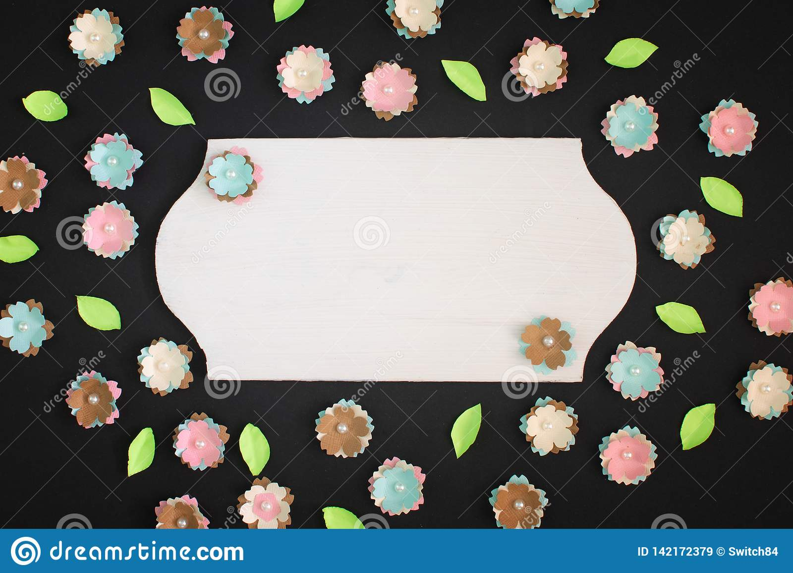 On A Black Background Small Flowers Made Of Paper Are Randomly