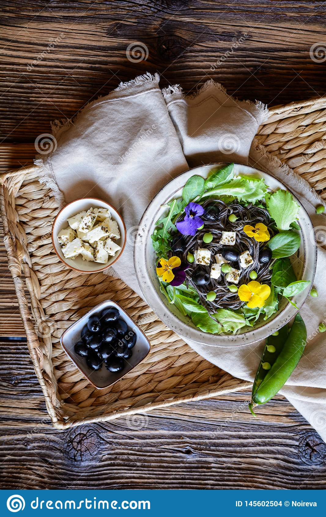 Black bean pasta salad with leafy greens, olives, green peas, sheep cheese and edible flowers
