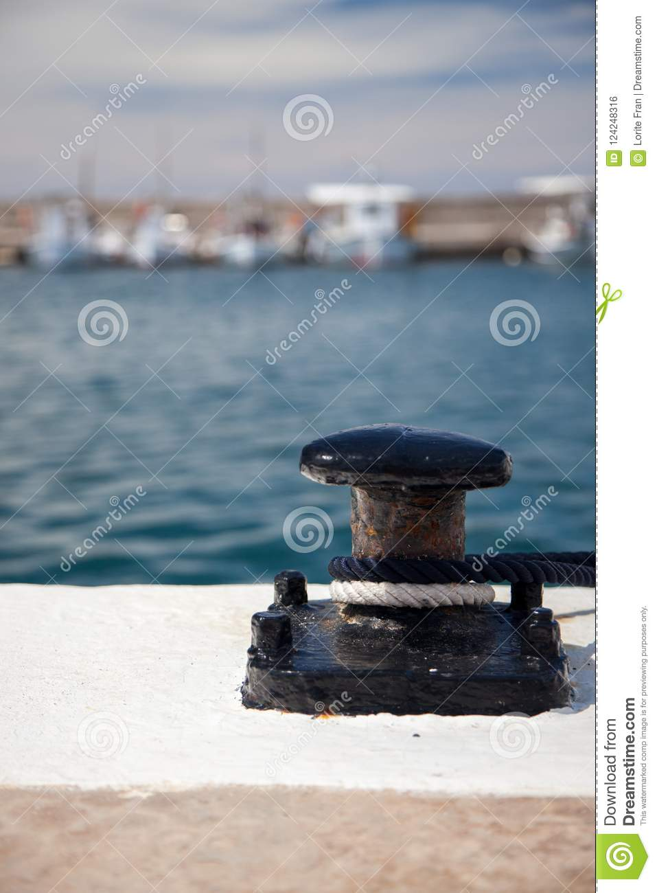 Black bollard with ropes in a marina with small fishing boats in the background