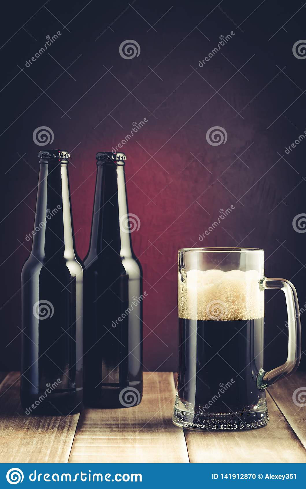 Black bottle and glass beer on a dark background with red light/black bottle and glass beer on a dark background with red light.