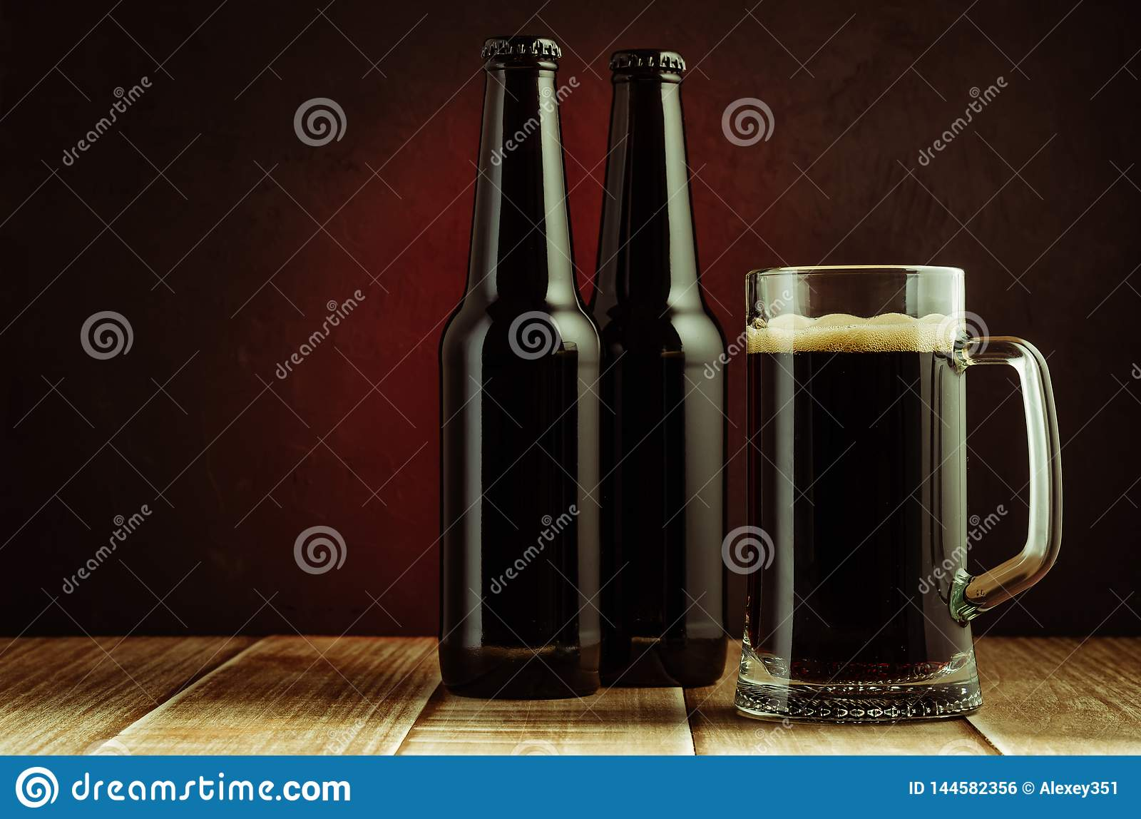 black bottle and glass beer on a red background/black bottle and glass beer on a red background of a wooden shelf. Copyspace and