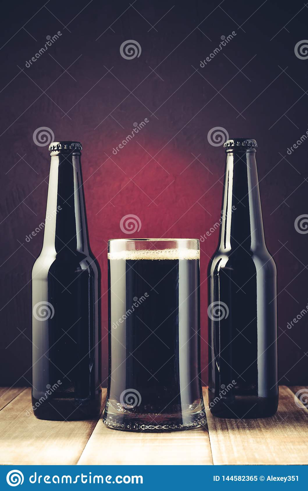 black bottle and glass beer on a red background/black bottle and glass beer on a red background of a wooden shelf. Toned