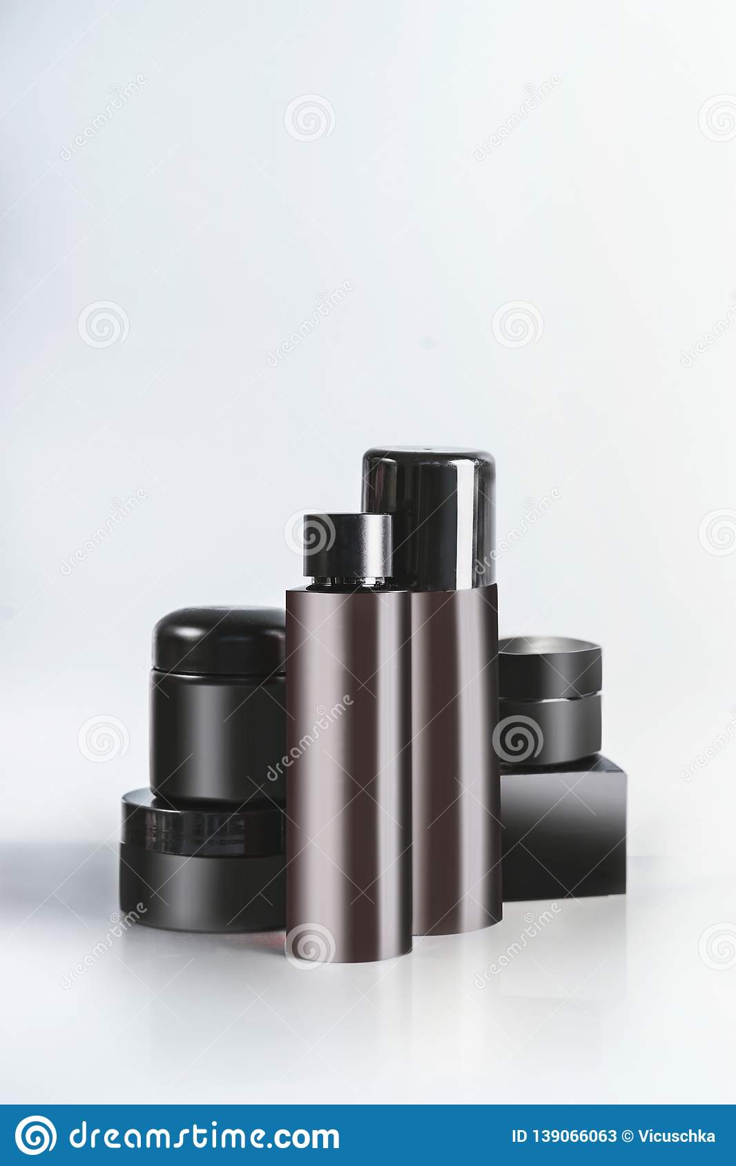 Black and brown cosmetic product jars and bottles with branding mock up, standing on light table at wall background. Snail mucin