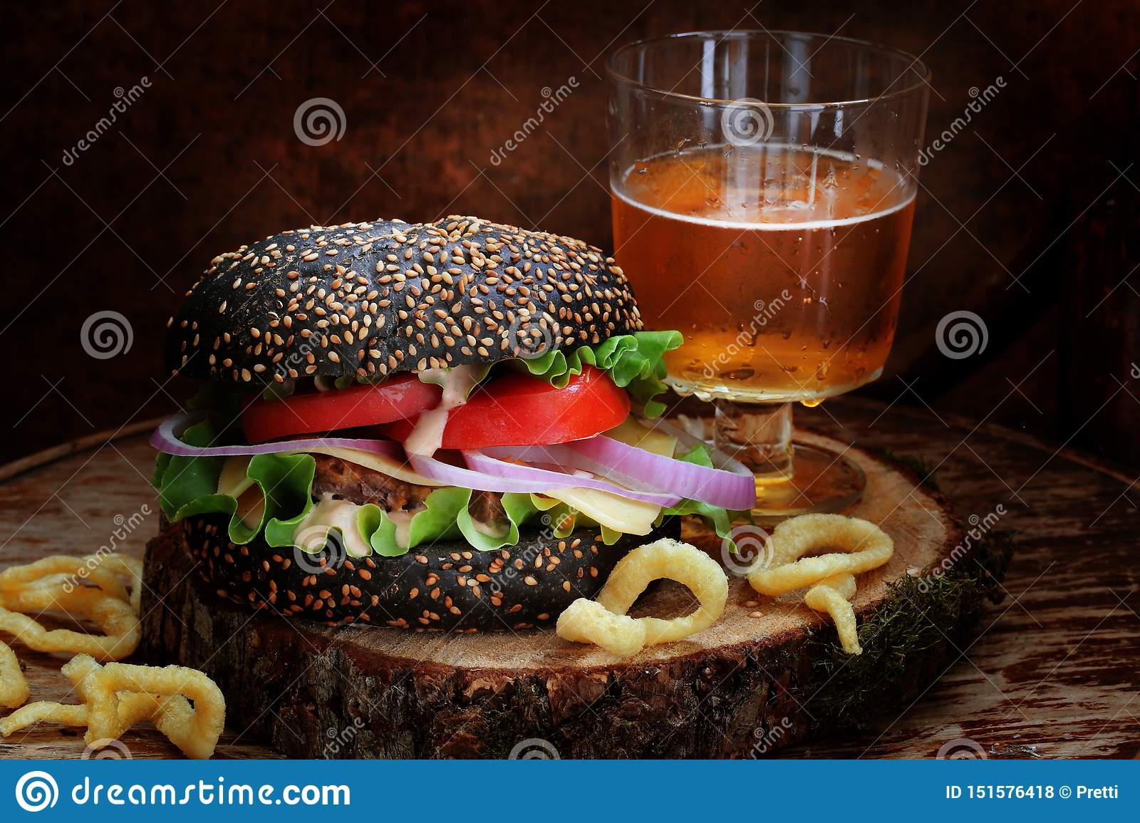 Black burger with beer and onion rings