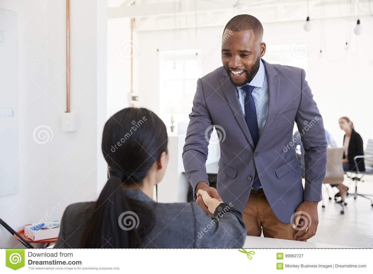 Black businessman and seated woman shaking hands in office
