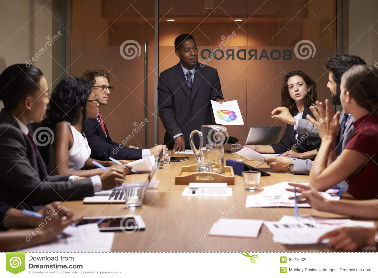 Black businessman stands to present to colleagues at meeting