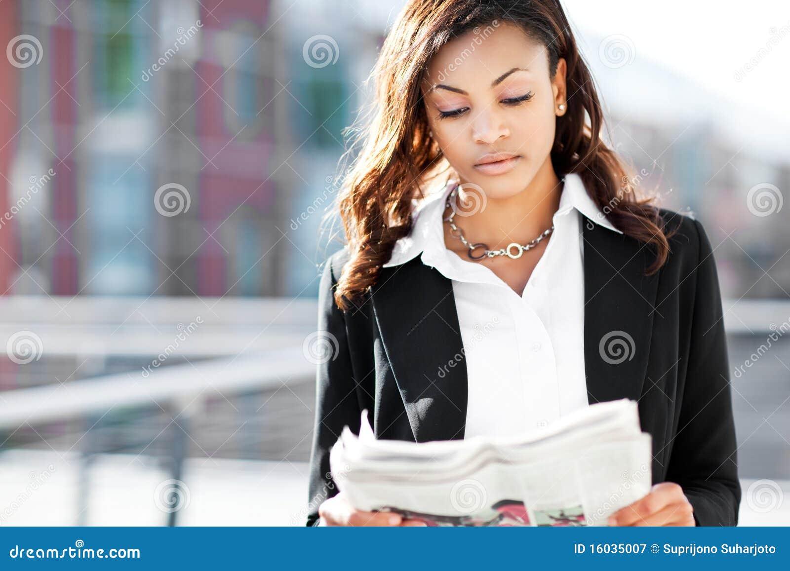 black businesswoman reading newspaper stock image - image of