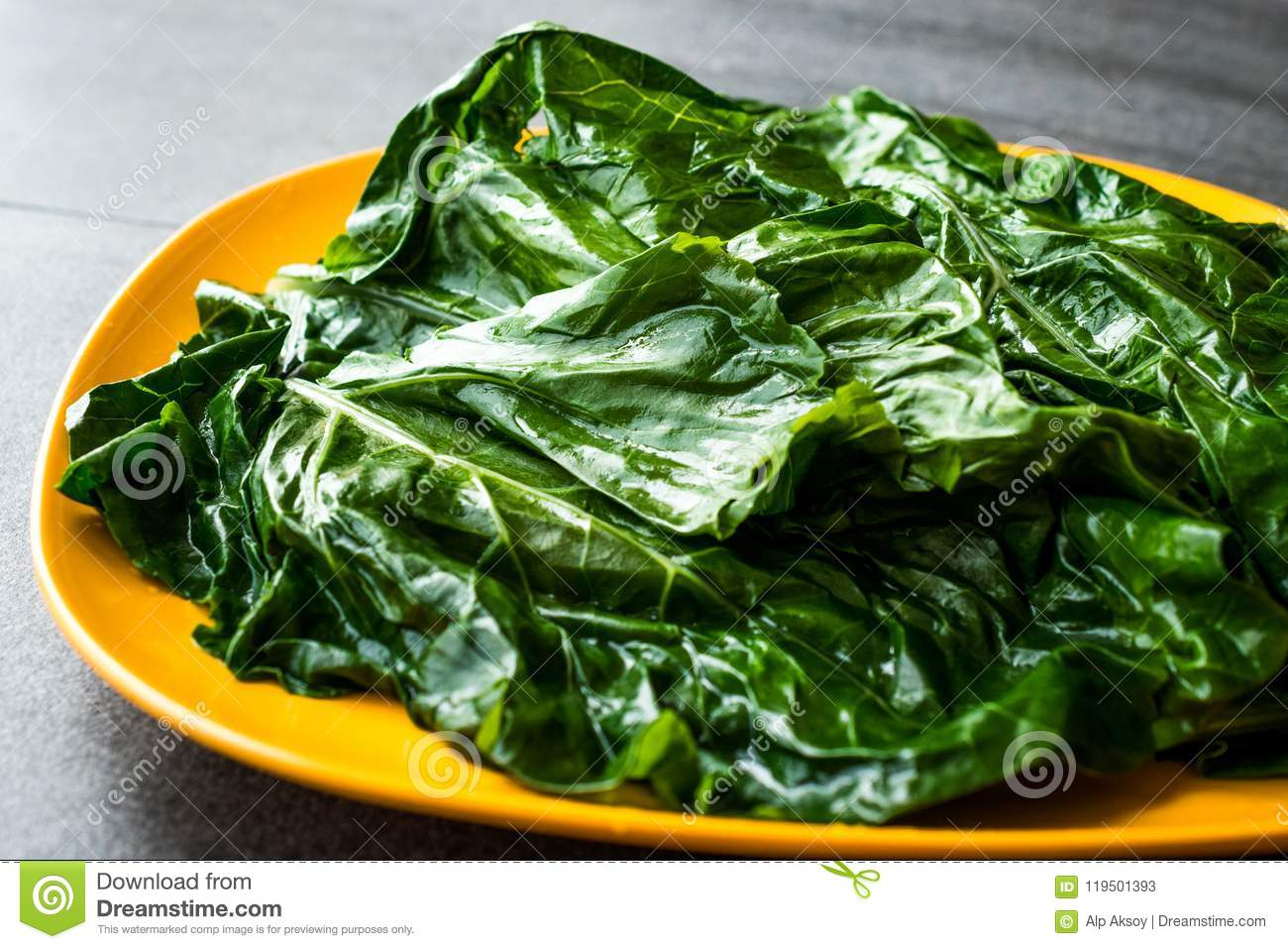 Black Cabbage Leaves / Organic Green Lacinato Kale on Yellow Plate with Grey Granit Surface