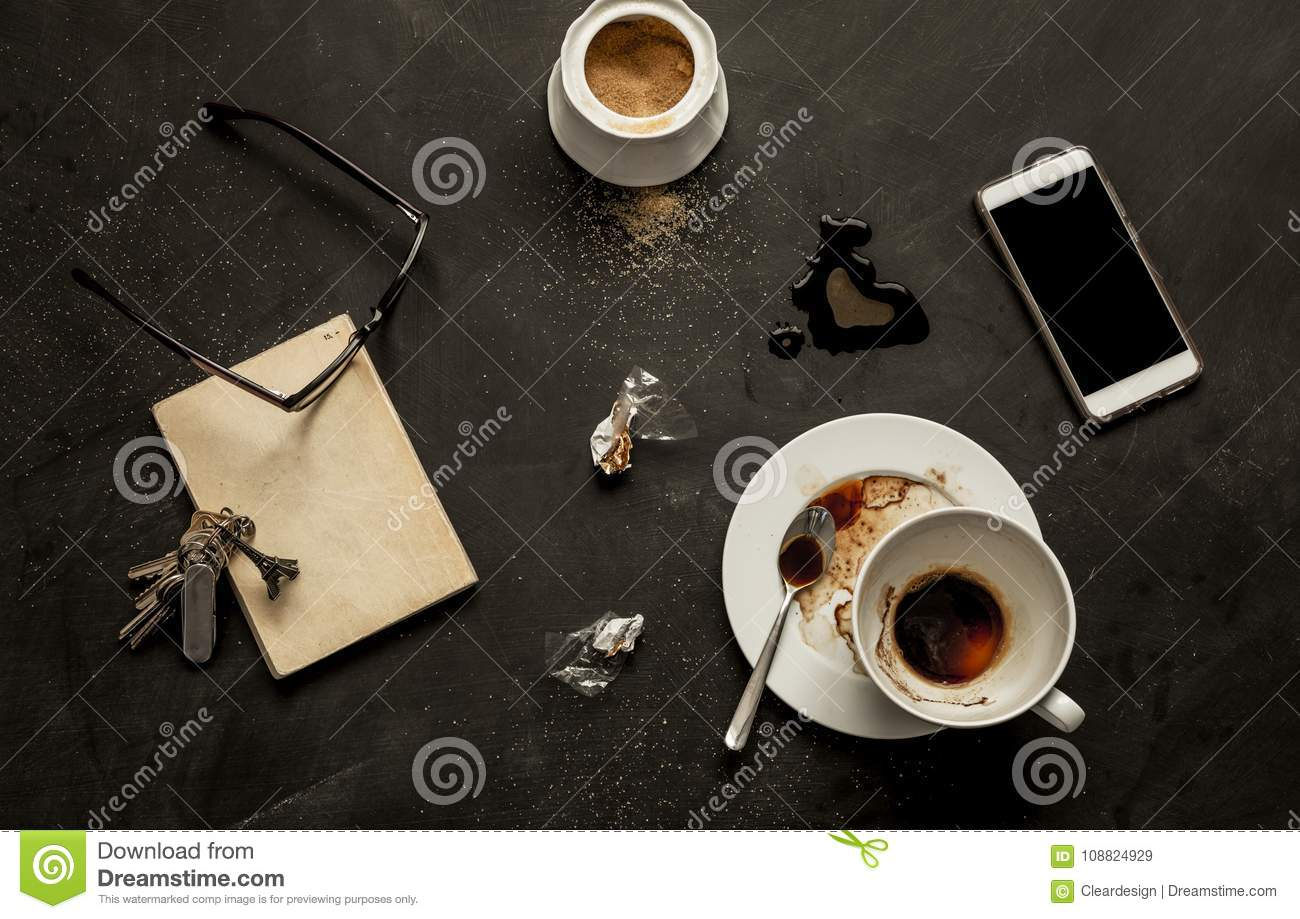 Black cafe table - empty coffee cup and smartphone