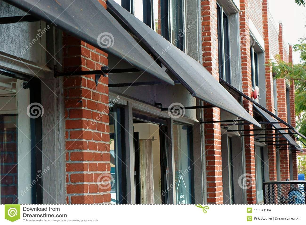 Black Canvas Awnings Projecting Out From A Brick Wall
