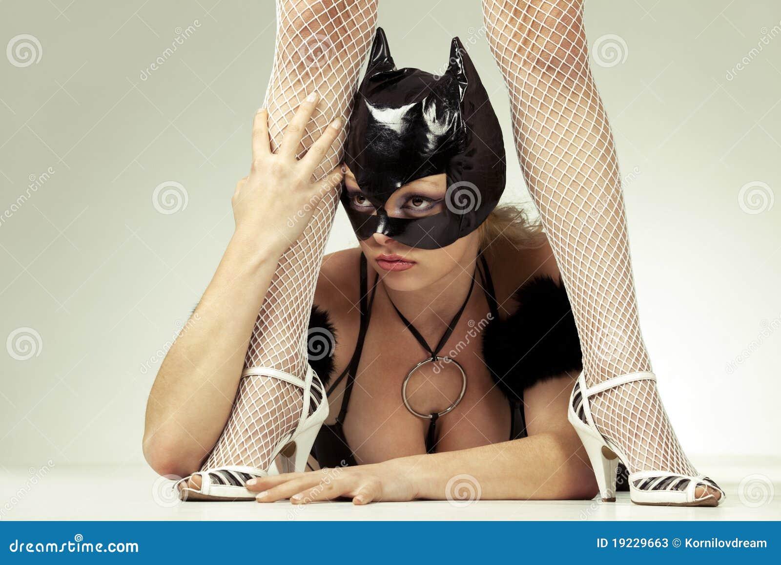 Black cat is next to dominatrix`s legs