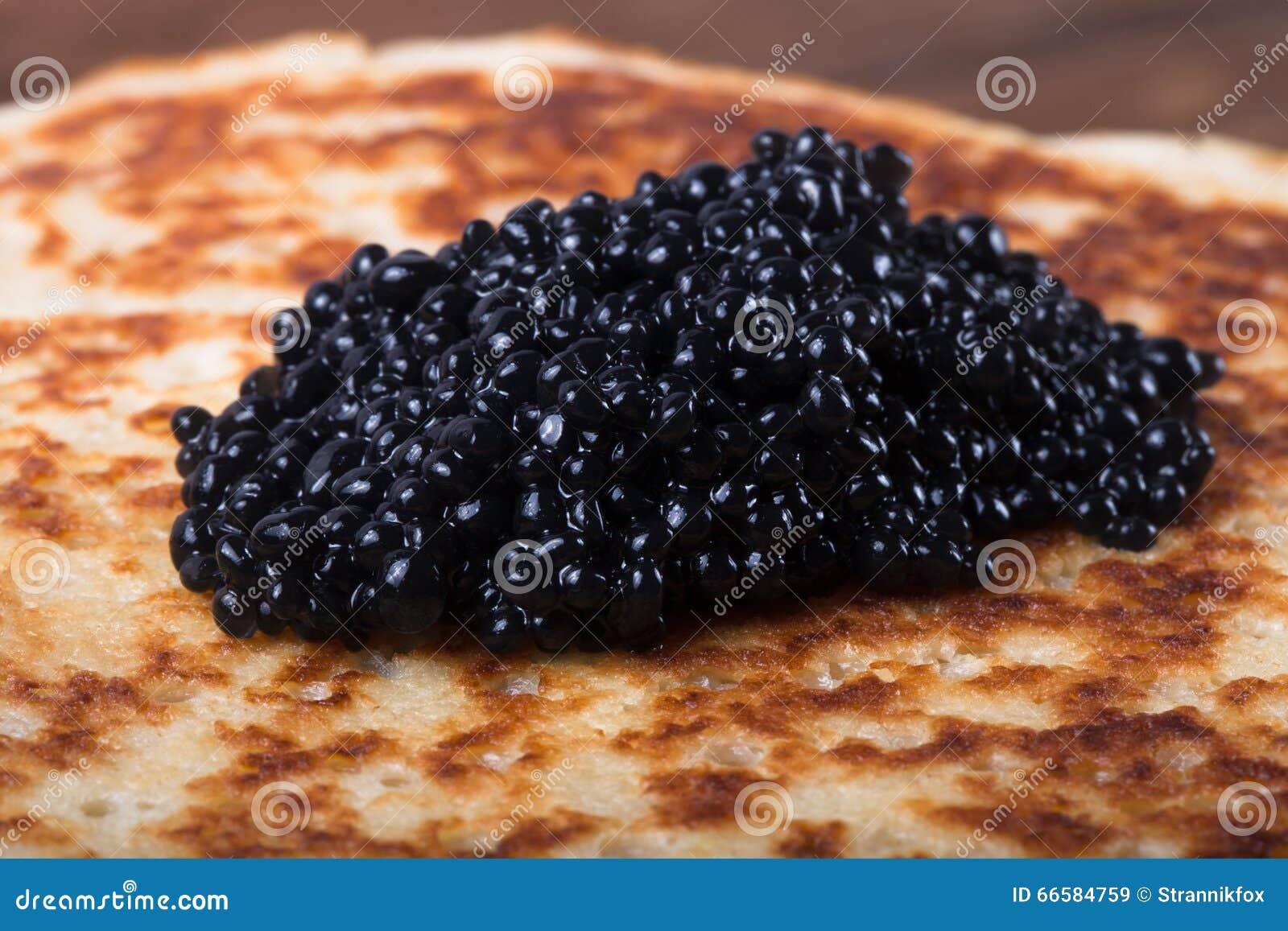 Black caviar on Russian pancakes - blini. Selective focus