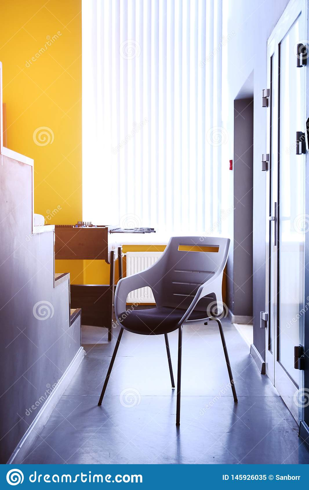 Black chair in the hallway of the apartment, a real photo with a copy of the space on the white wall. Beautiful office space. The