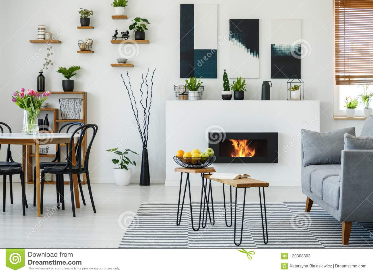 Black Chairs At Dining Table With Flowers In Flat Interior Grey Sofa Next To Fireplace Real Photo
