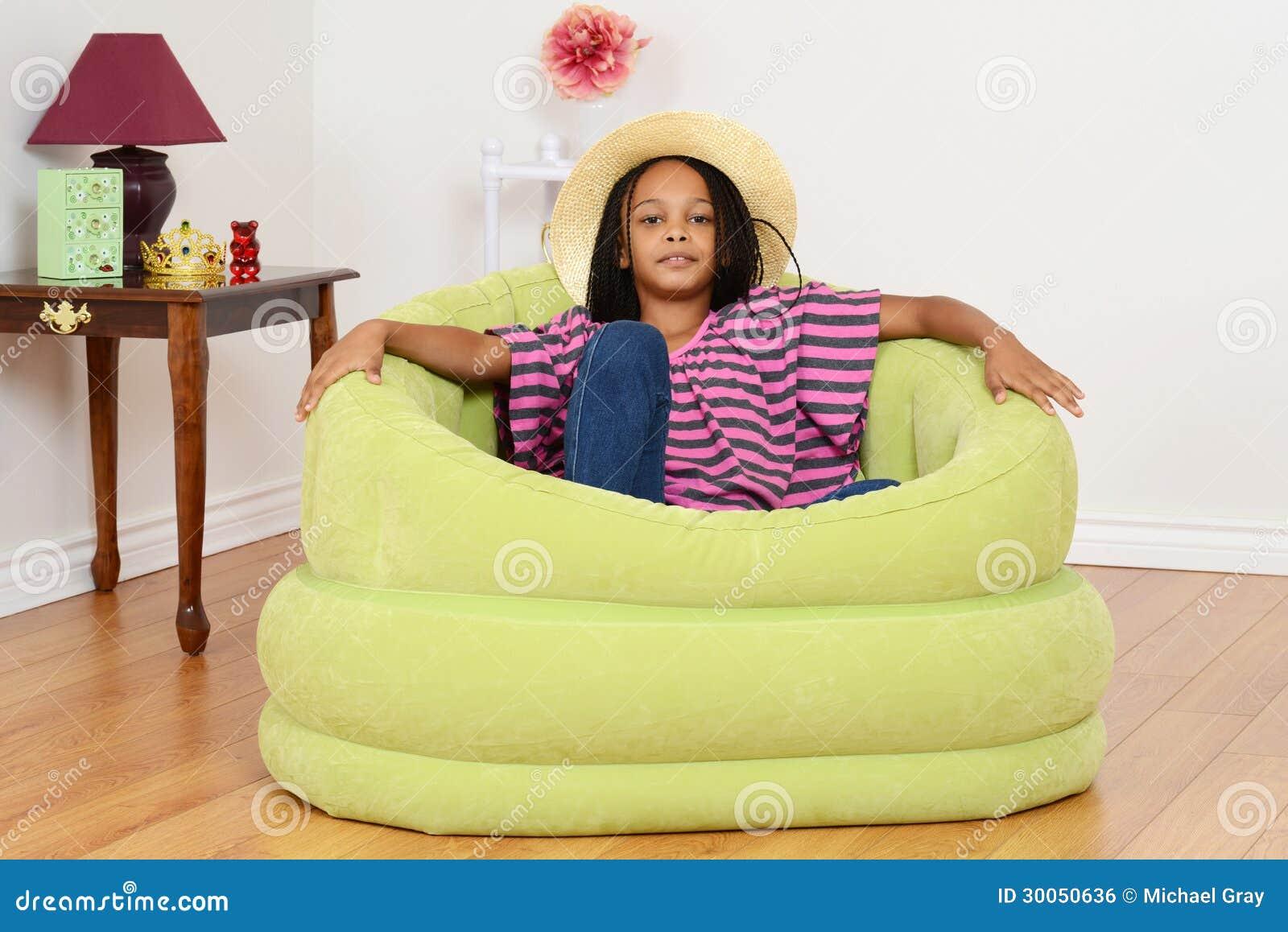 Black child sitting in chair -
