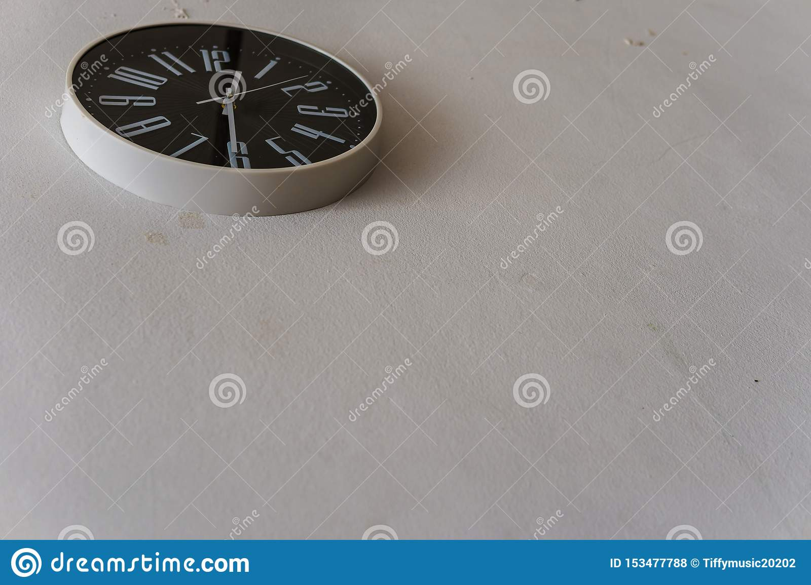 Black clock hanging on the white wall