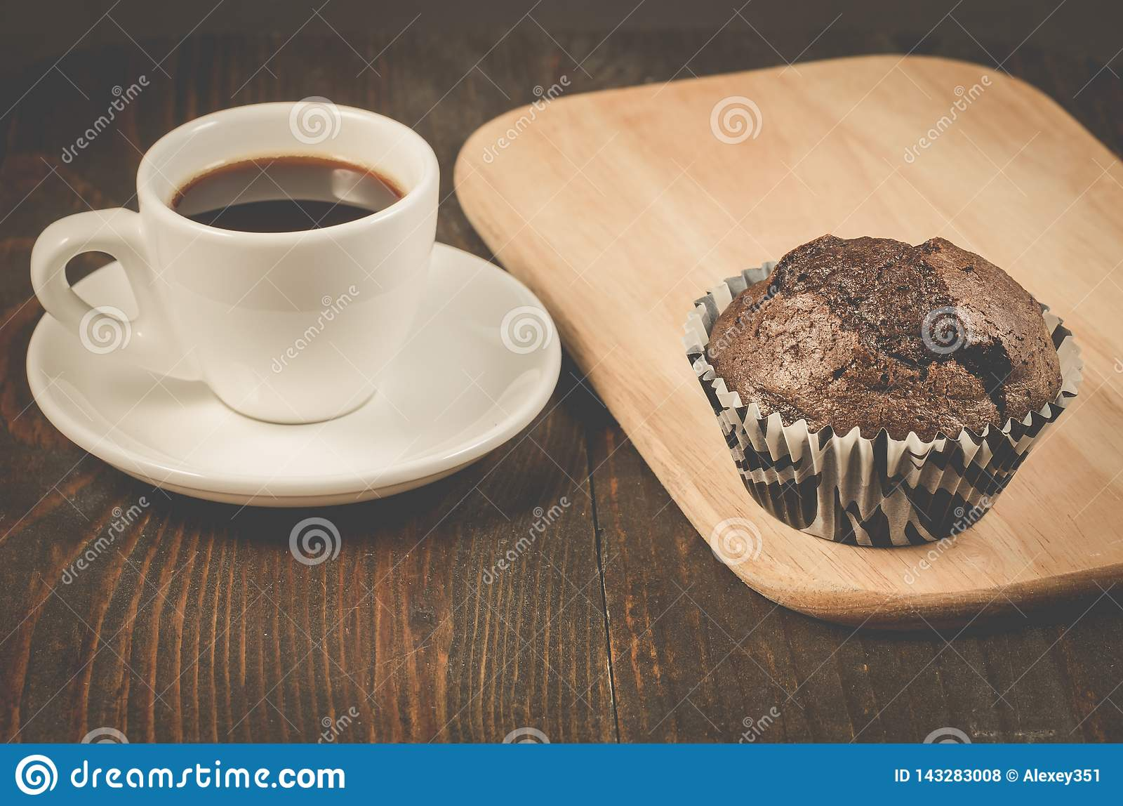 black coffee cup, chocolate muffin and wooden tray/black coffee cup, chocolate muffin and wooden tray, selective focus