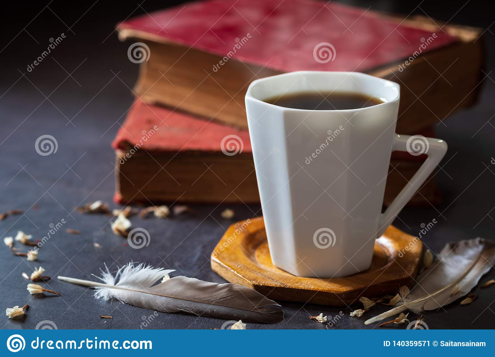 Black coffee in white cup and old books with feather and dried flower petals.