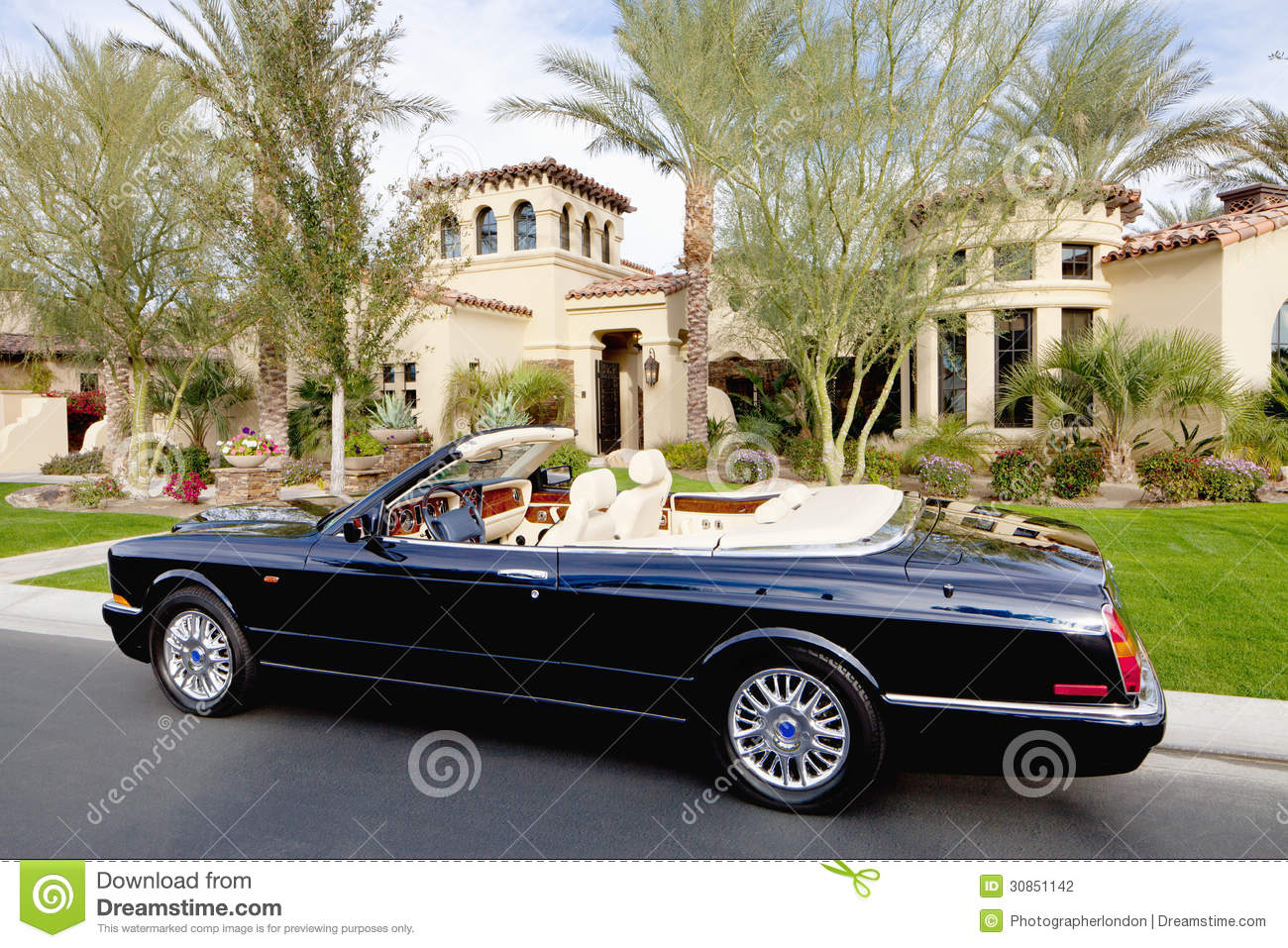 Luxury House And Car luxurious convertible car parked in front of a mansion house stock