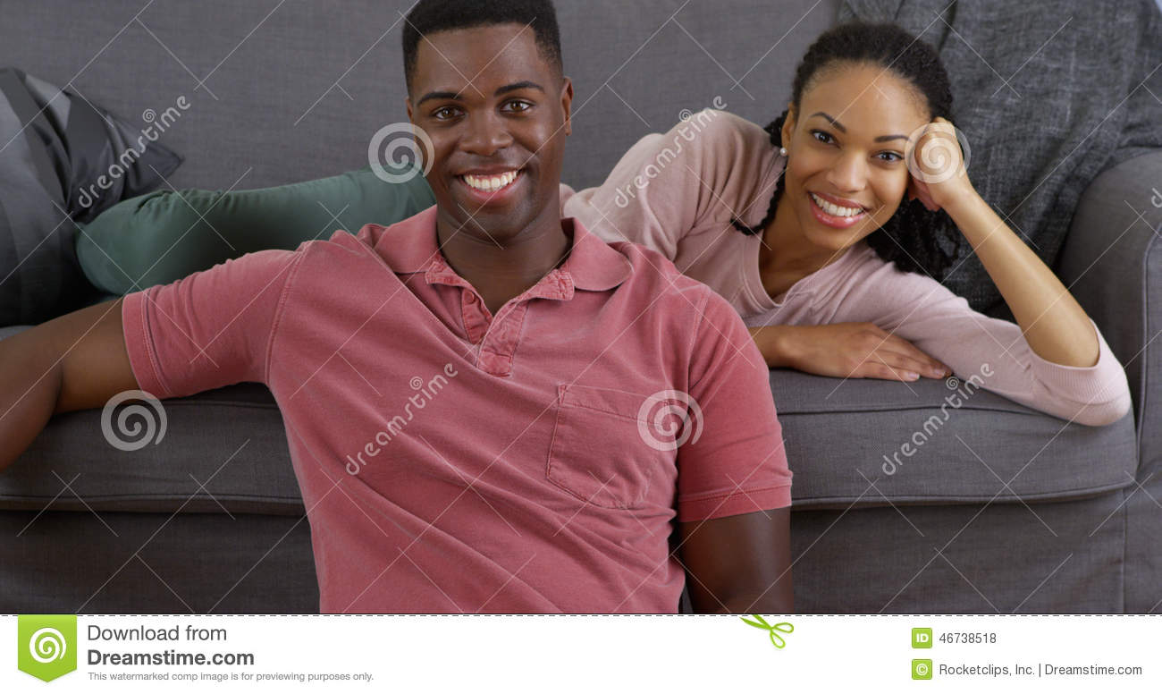 Black couple relaxing on couch and smiling at camera