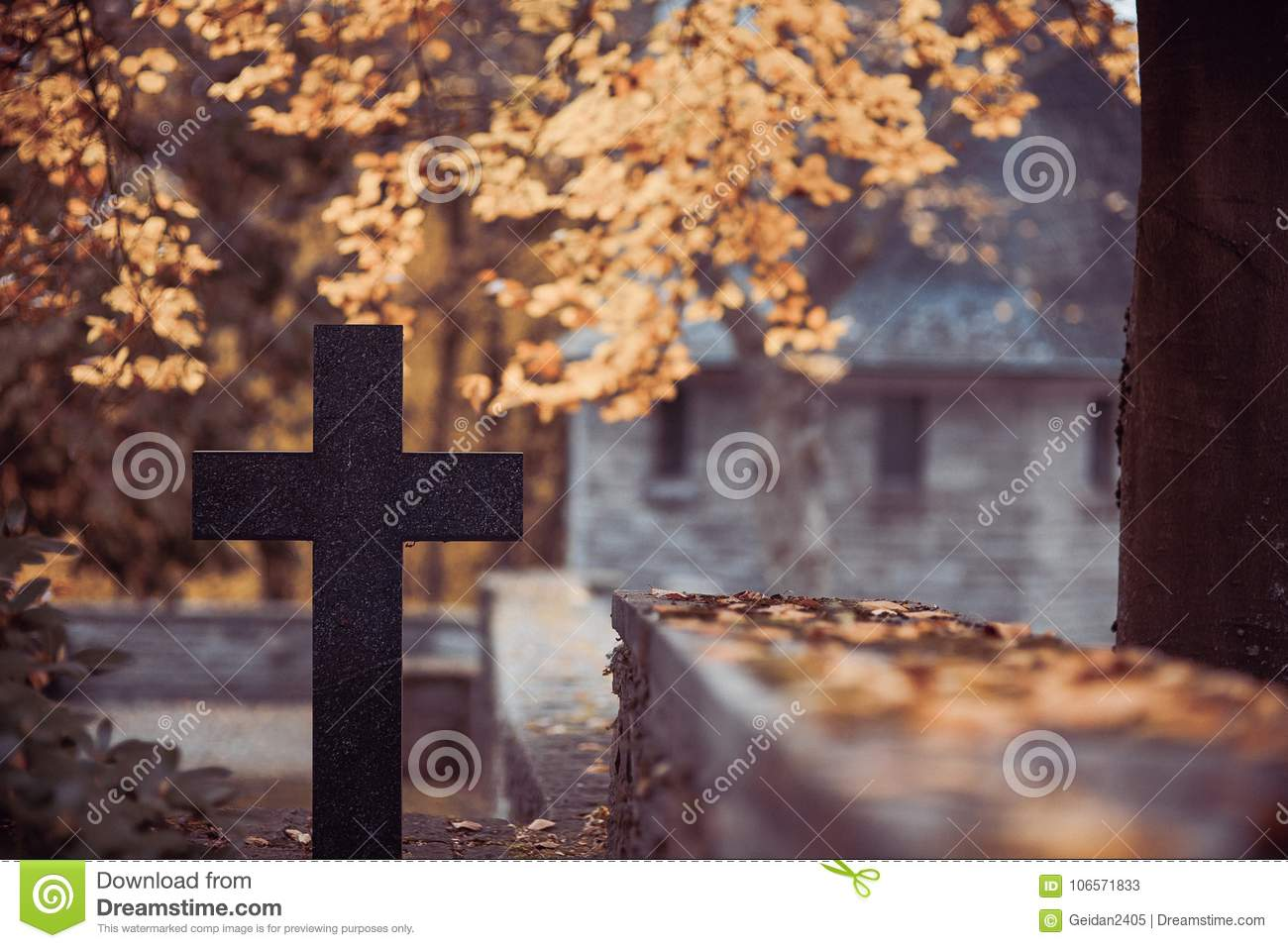 Black cross in the cemetery with mausoleum