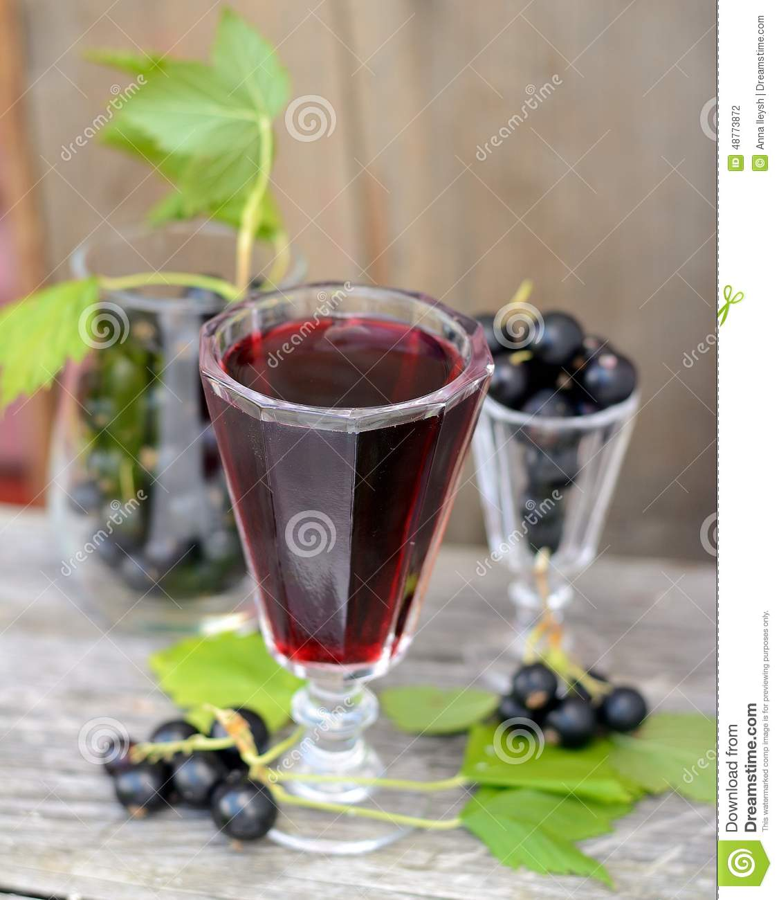 Black currant liquor and ripe berries on wooden