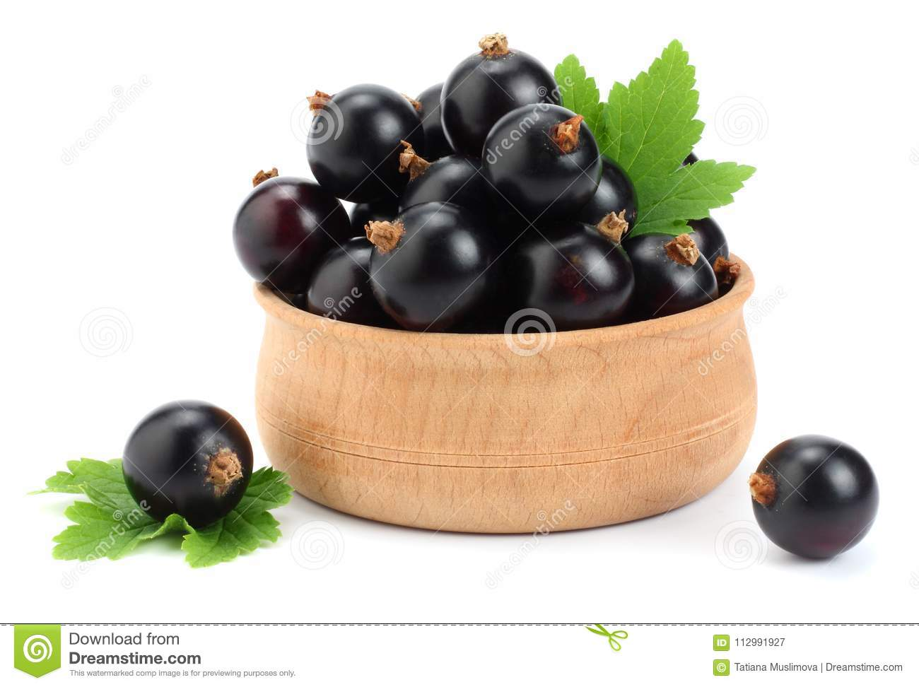black currant in wooden bowl with green leaf isolated on white background