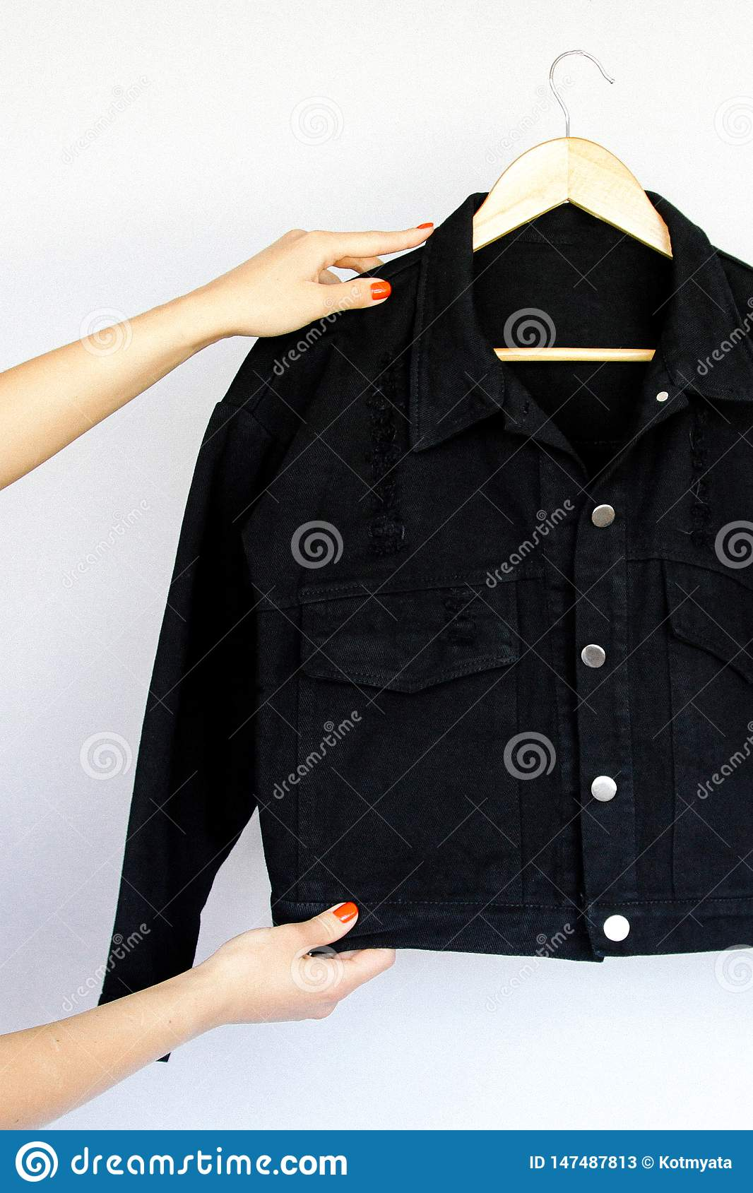 Black denim jacket on a hanger and women`s hands with a red manicure on an background.