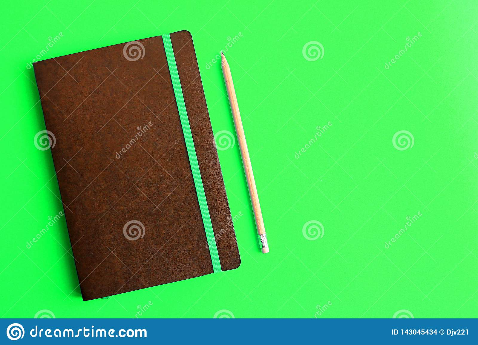 Black diary next to a pencil on a green background