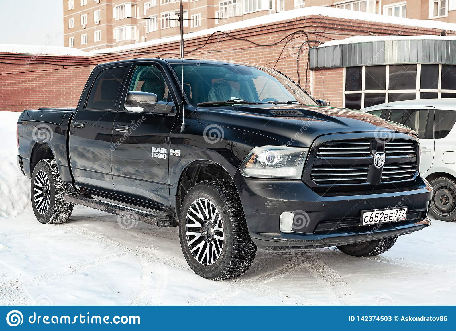 Black Dodge Ram with an engine of 5.7 liters front view on the car parking with snow background