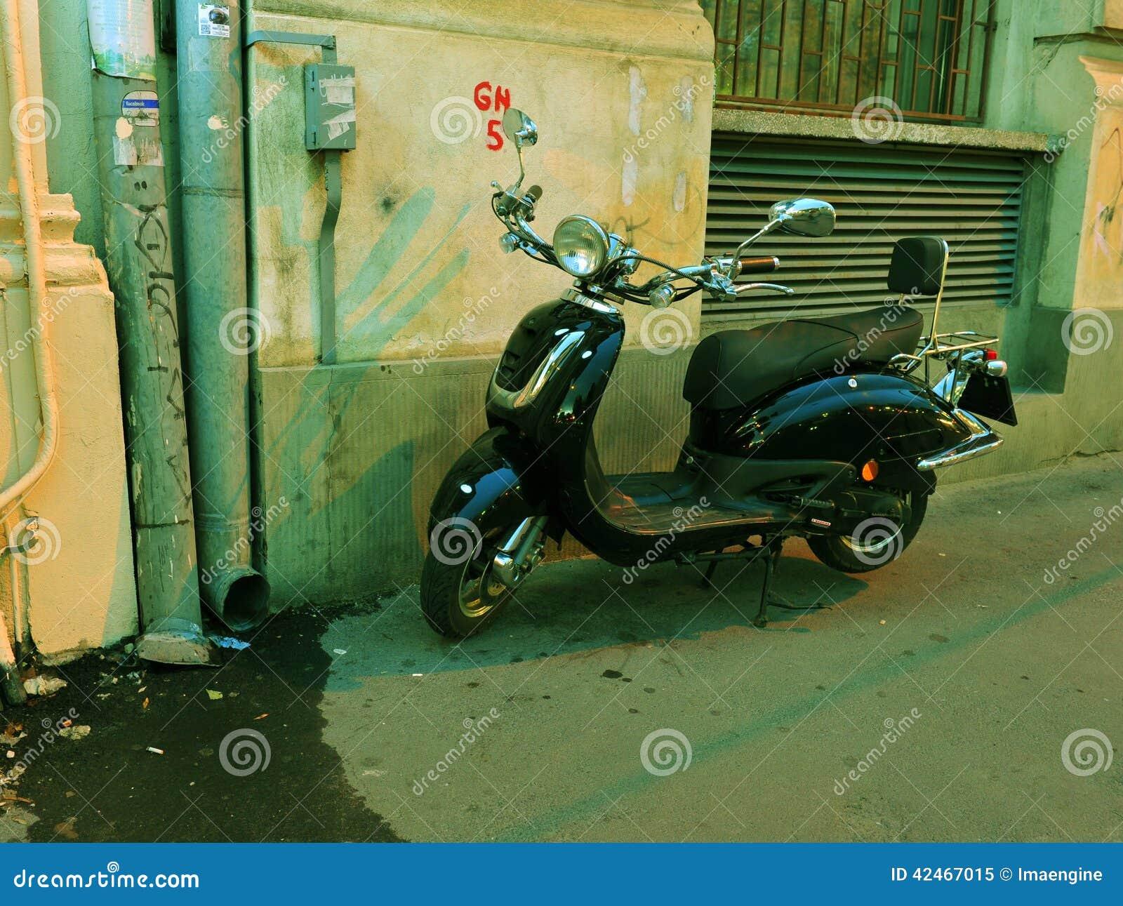 black elegant scooter parked on the sidewalk royalty free stock photography. Black Bedroom Furniture Sets. Home Design Ideas