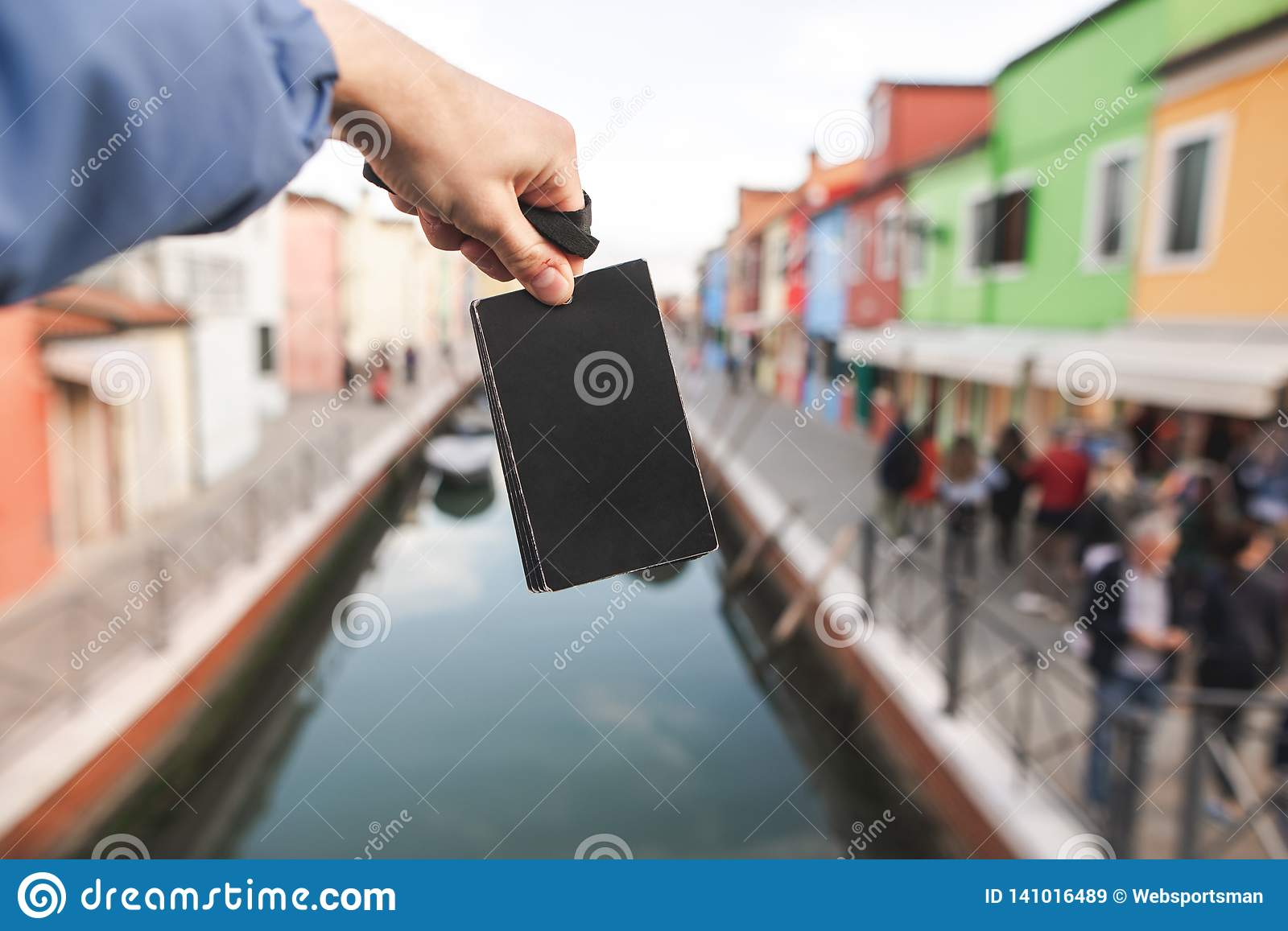 Black empty card in the hands of a young man on the background of colored houses and canal of Burano island, Venice
