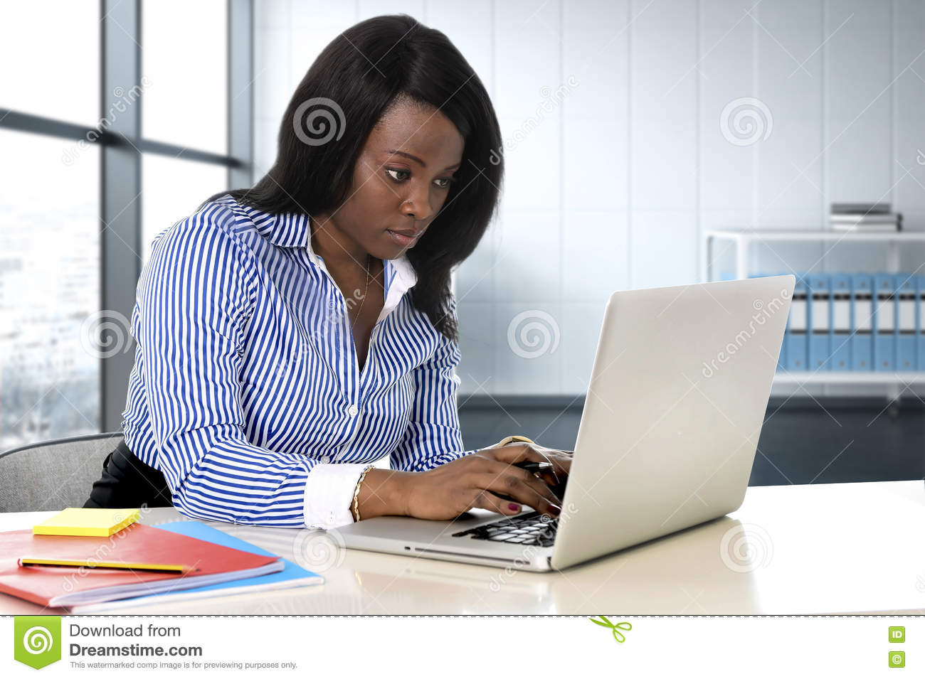 Black ethnicity woman sitting at computer laptop desk typing concentrated working