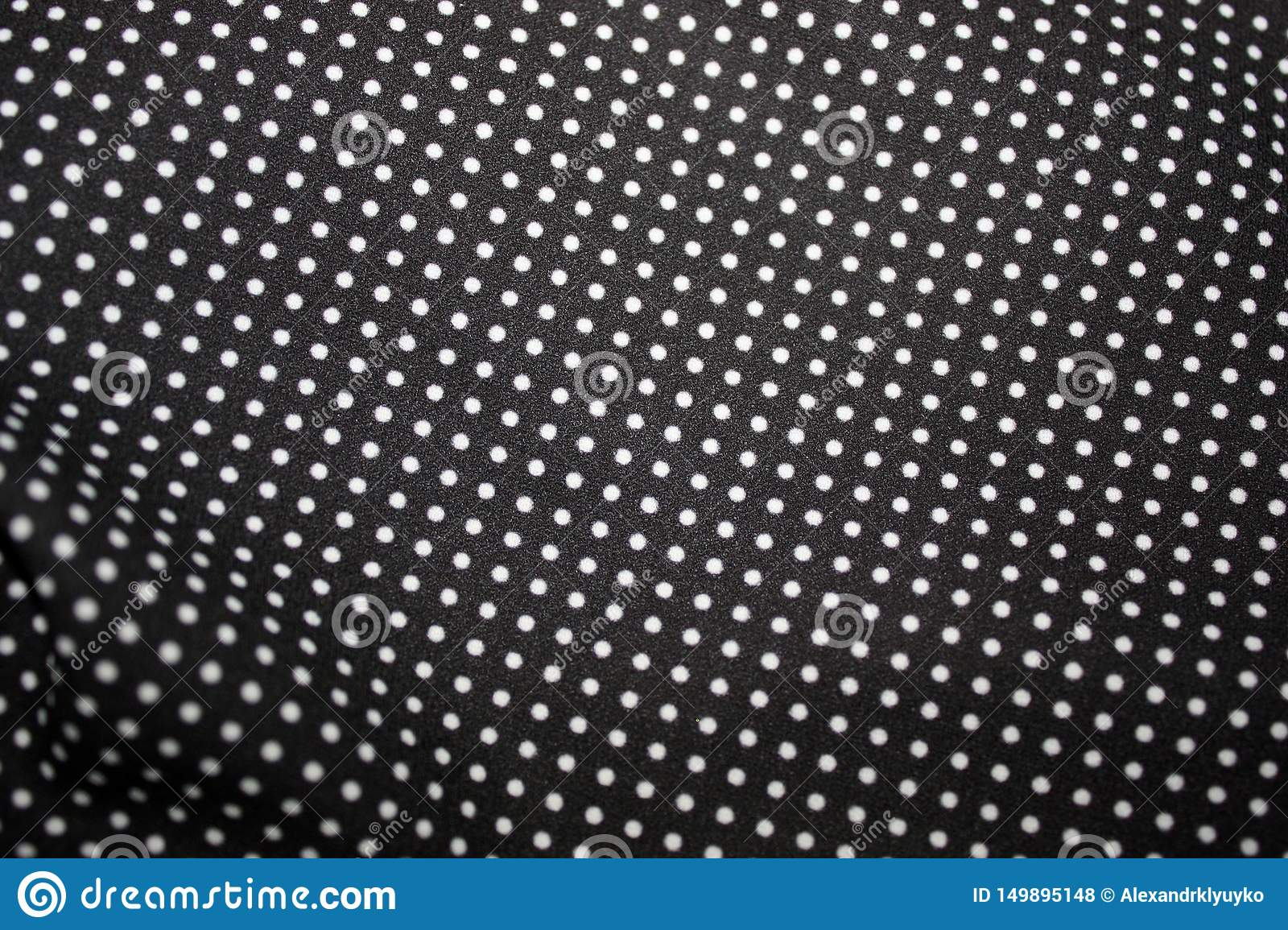 Black fabric and white tiny polka dot background, close-up