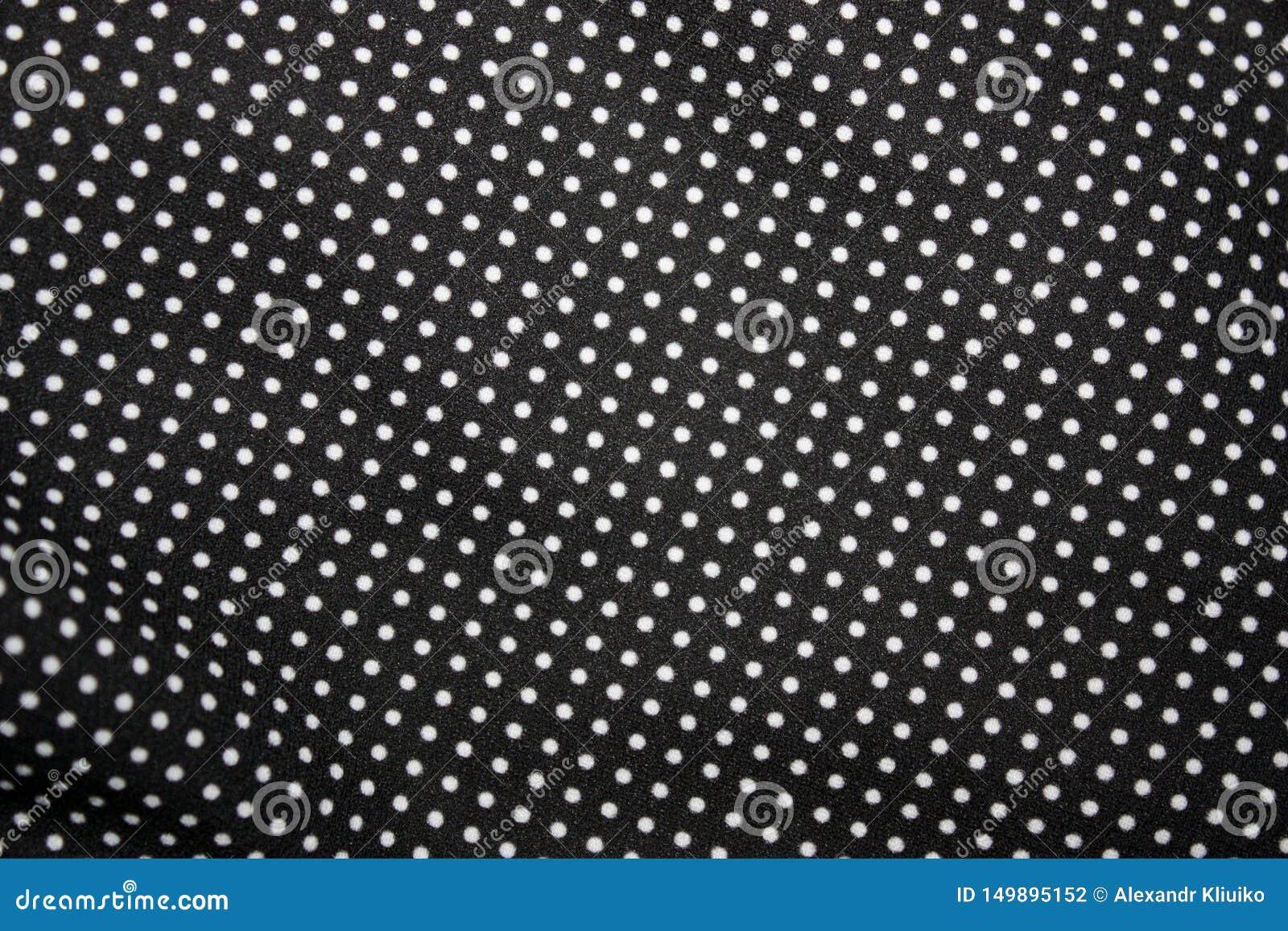Black fabric and white tiny polka dot background, close-up