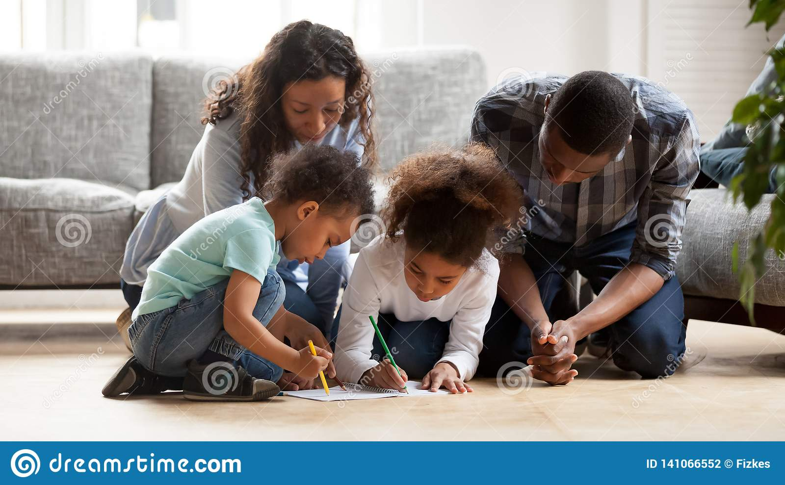 Black Family With Little Kids Painting Together In Living ...