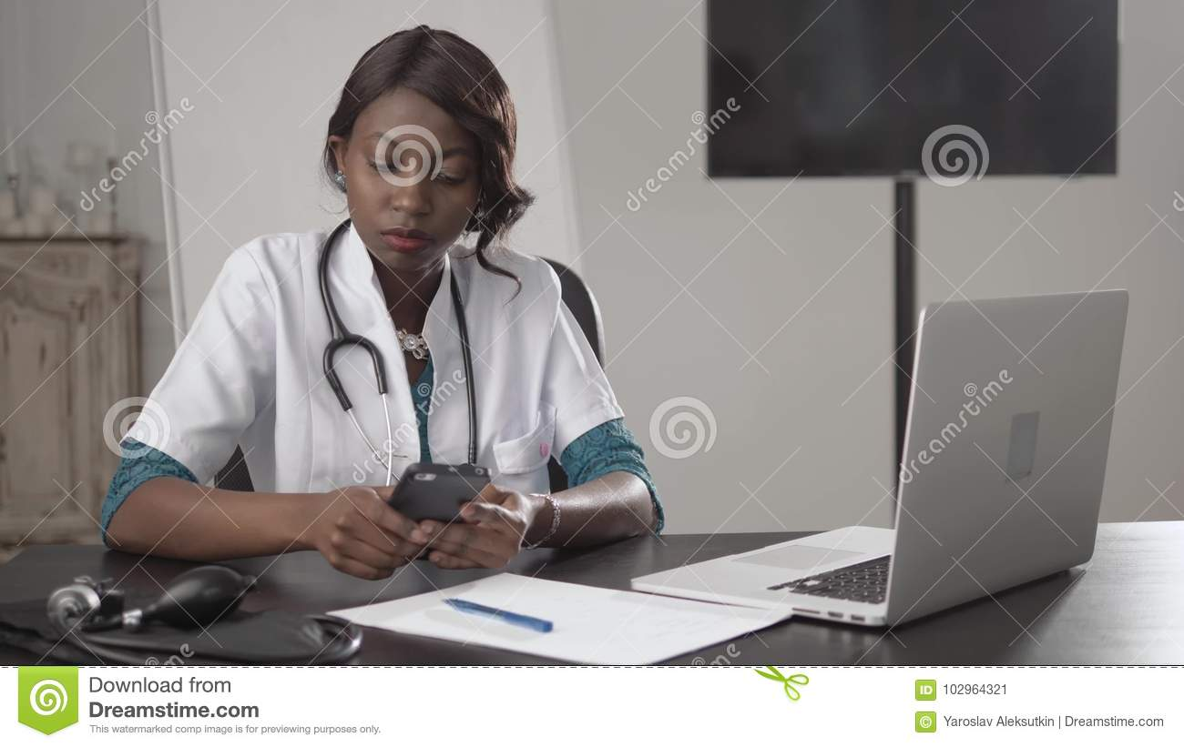 Black female doctor sits at an office desk looking to camera, african american nurse work on laptop in cabinet, modern