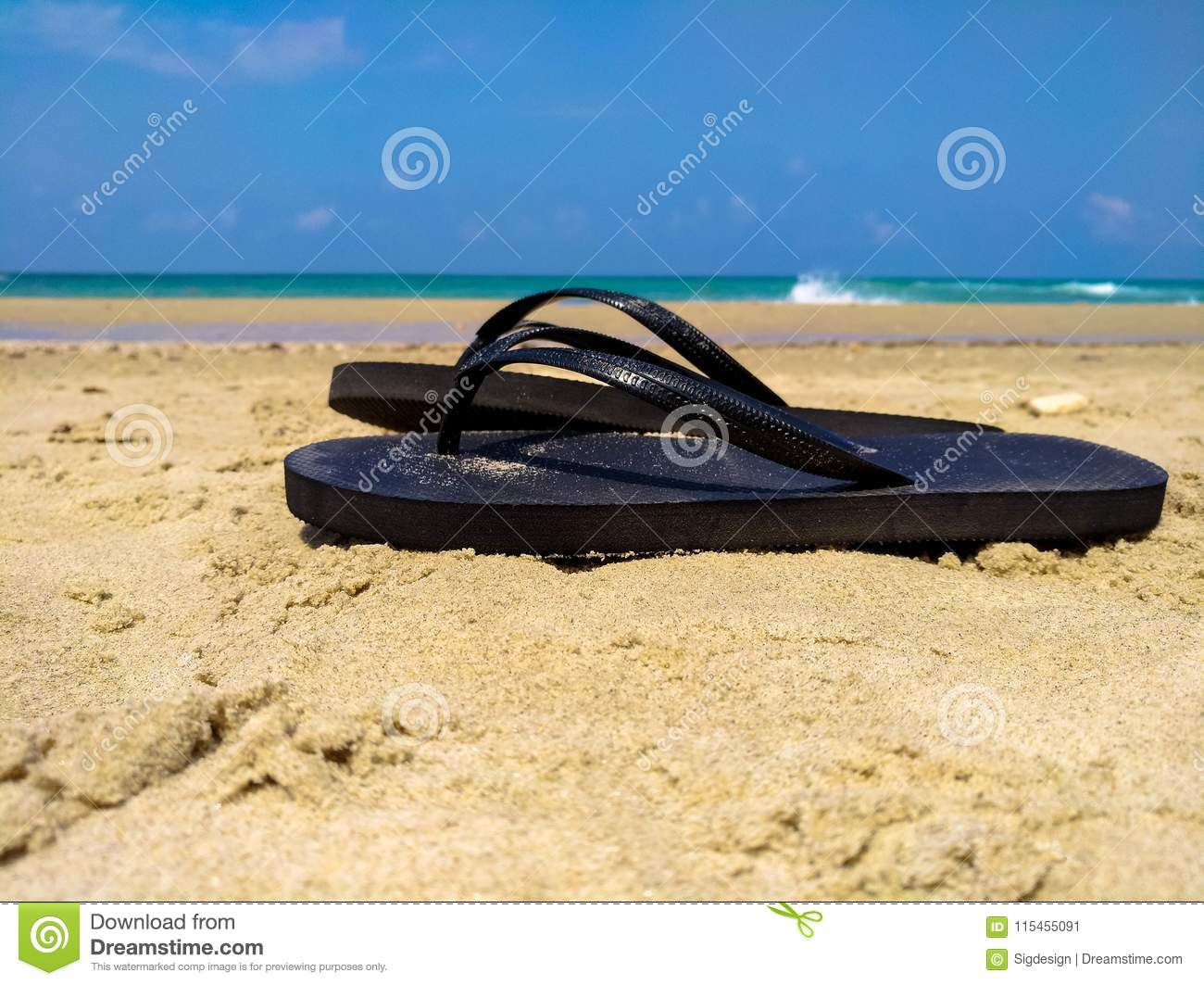 62381c6d1dce Black Flip Flops On A Sand With Blue Sea And Sky Background Stock ...