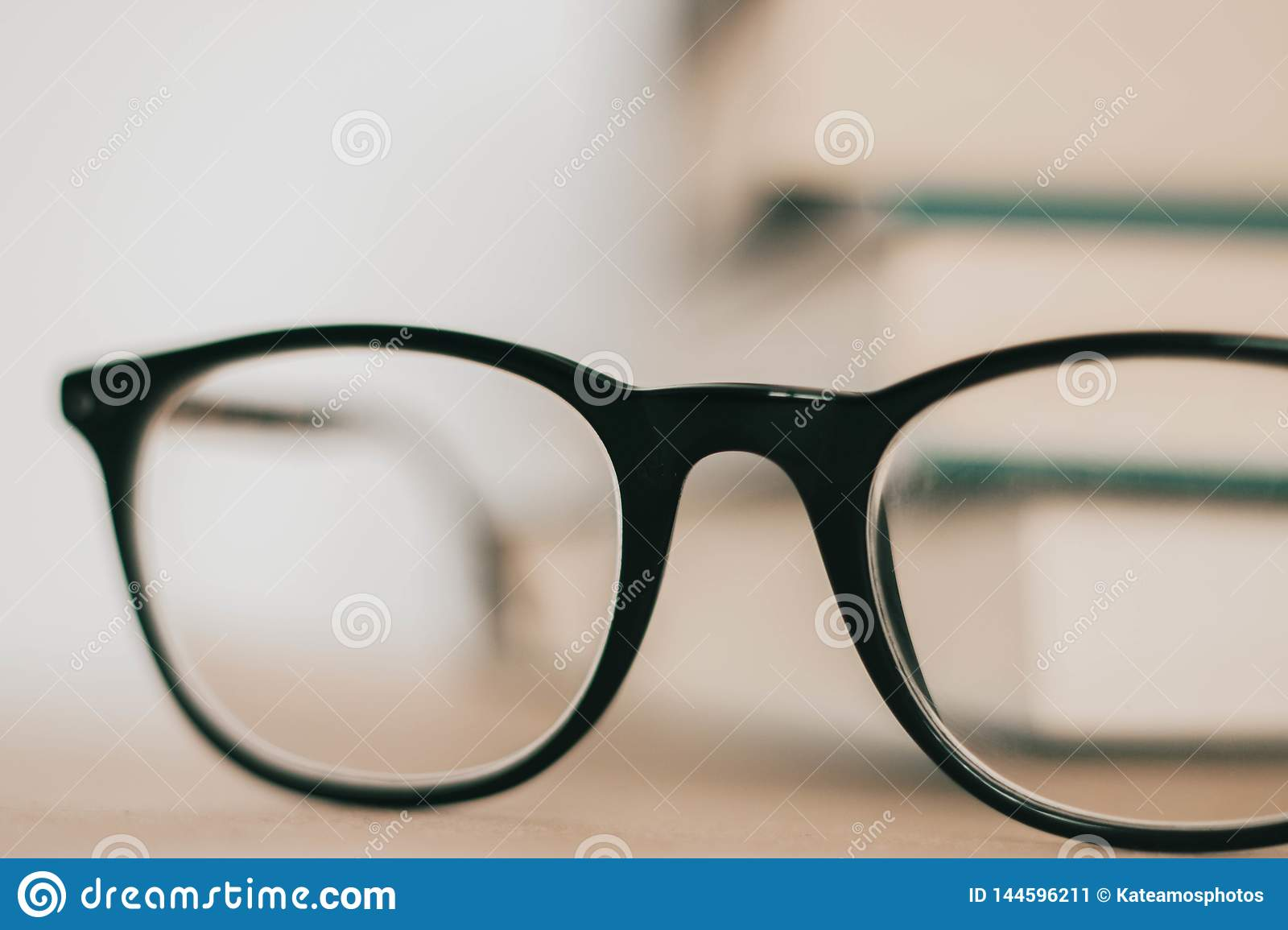 Black frame glasses in front of pile of books