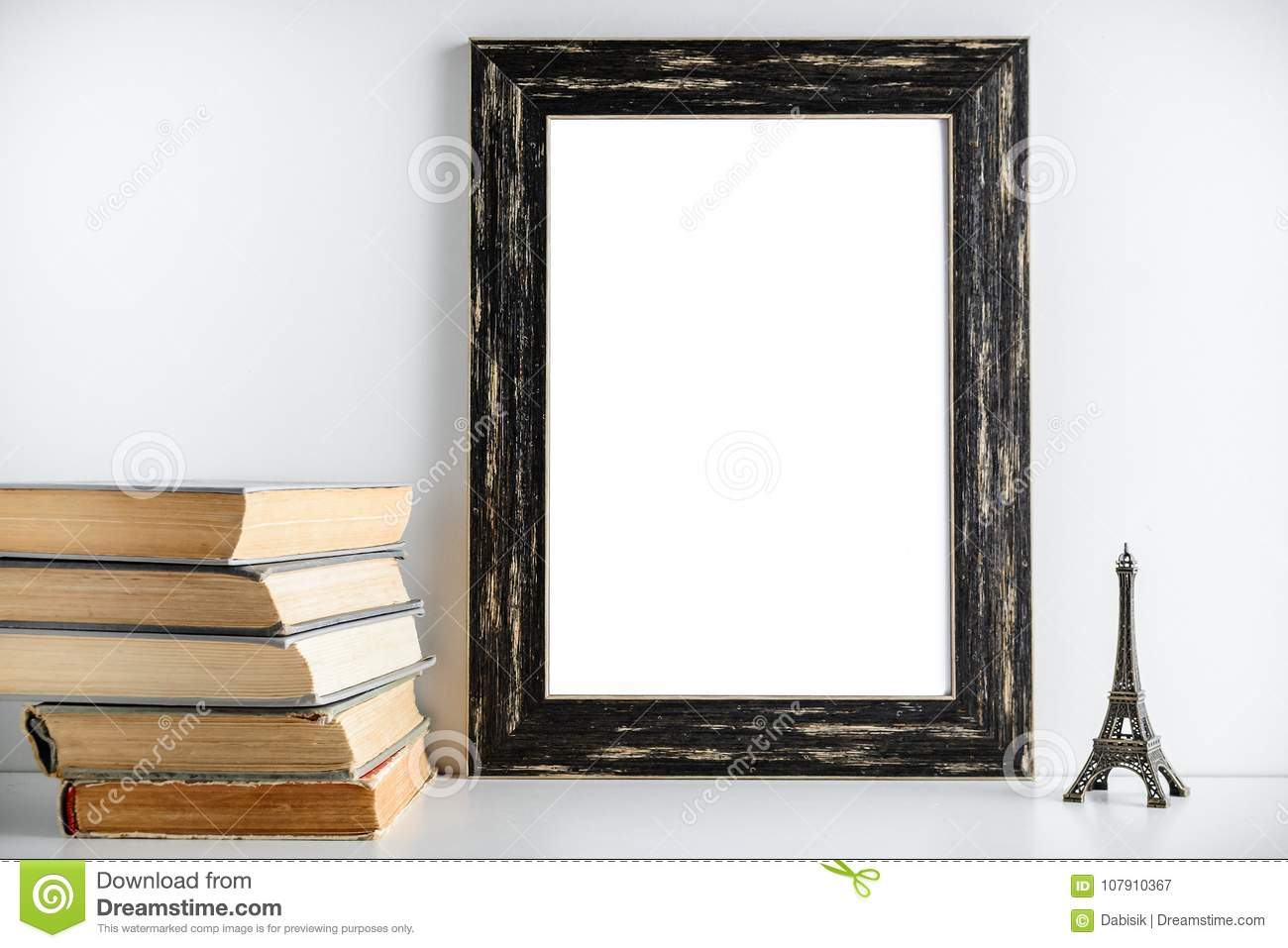 Black frame layout. Toy tower and old books near the frame on a