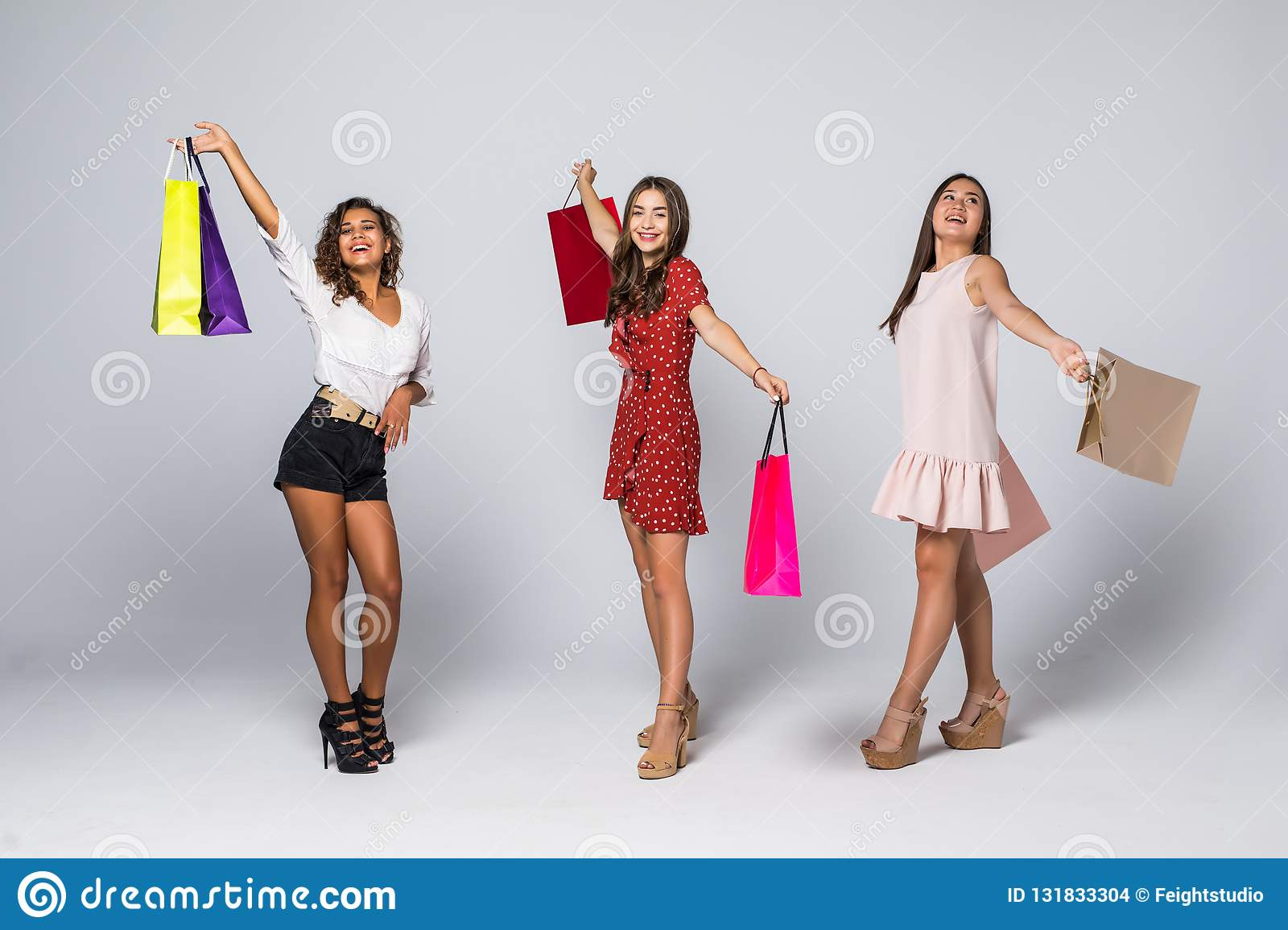 Black friday concept. Portrait of cheerful three mixed race women holding colorful bags in raised hands enjoying seasonal sales
