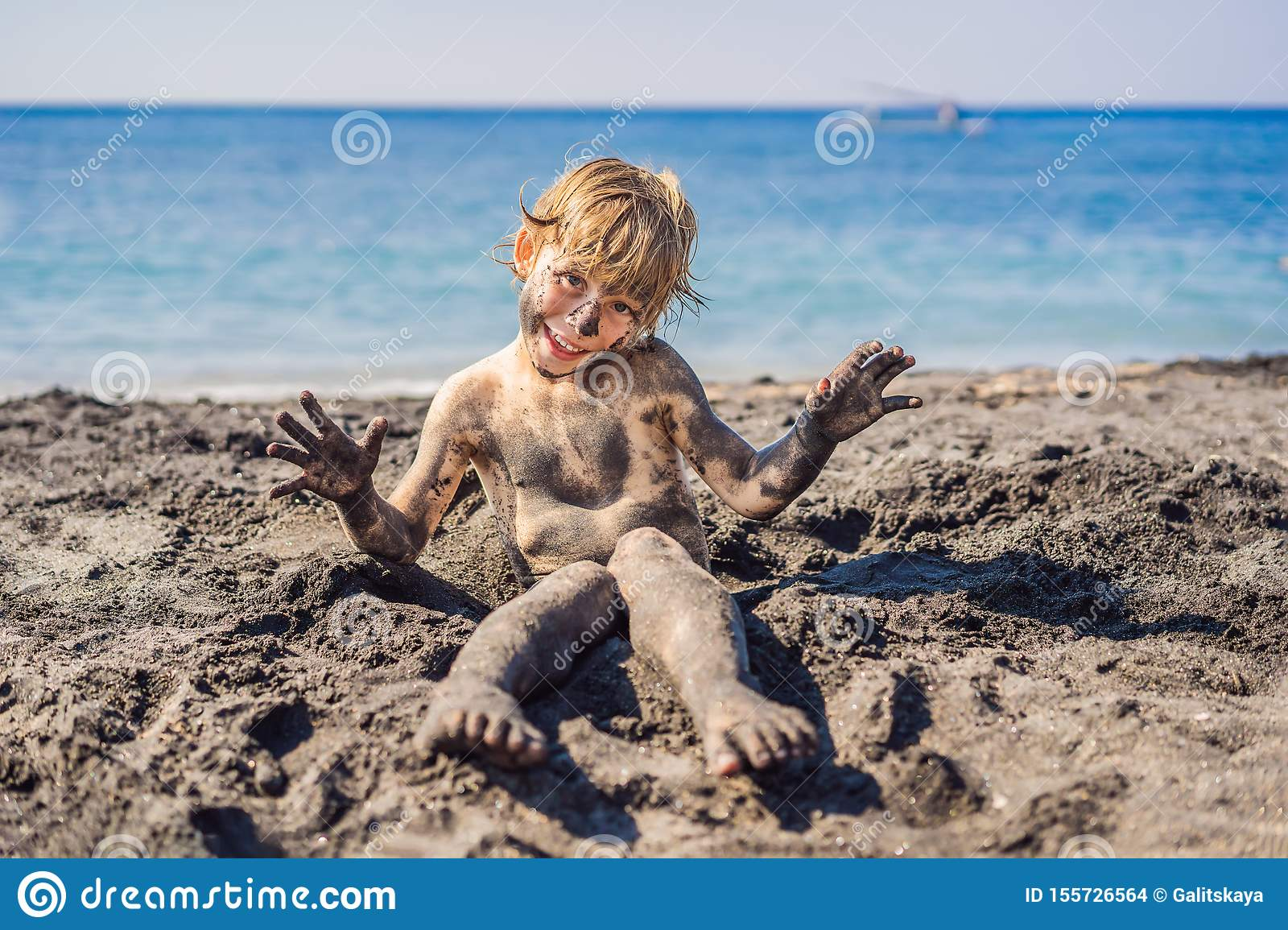 Black Friday concept. Smiling boy with dirty Black face sitting and playing on black sand sea beach before swimming in