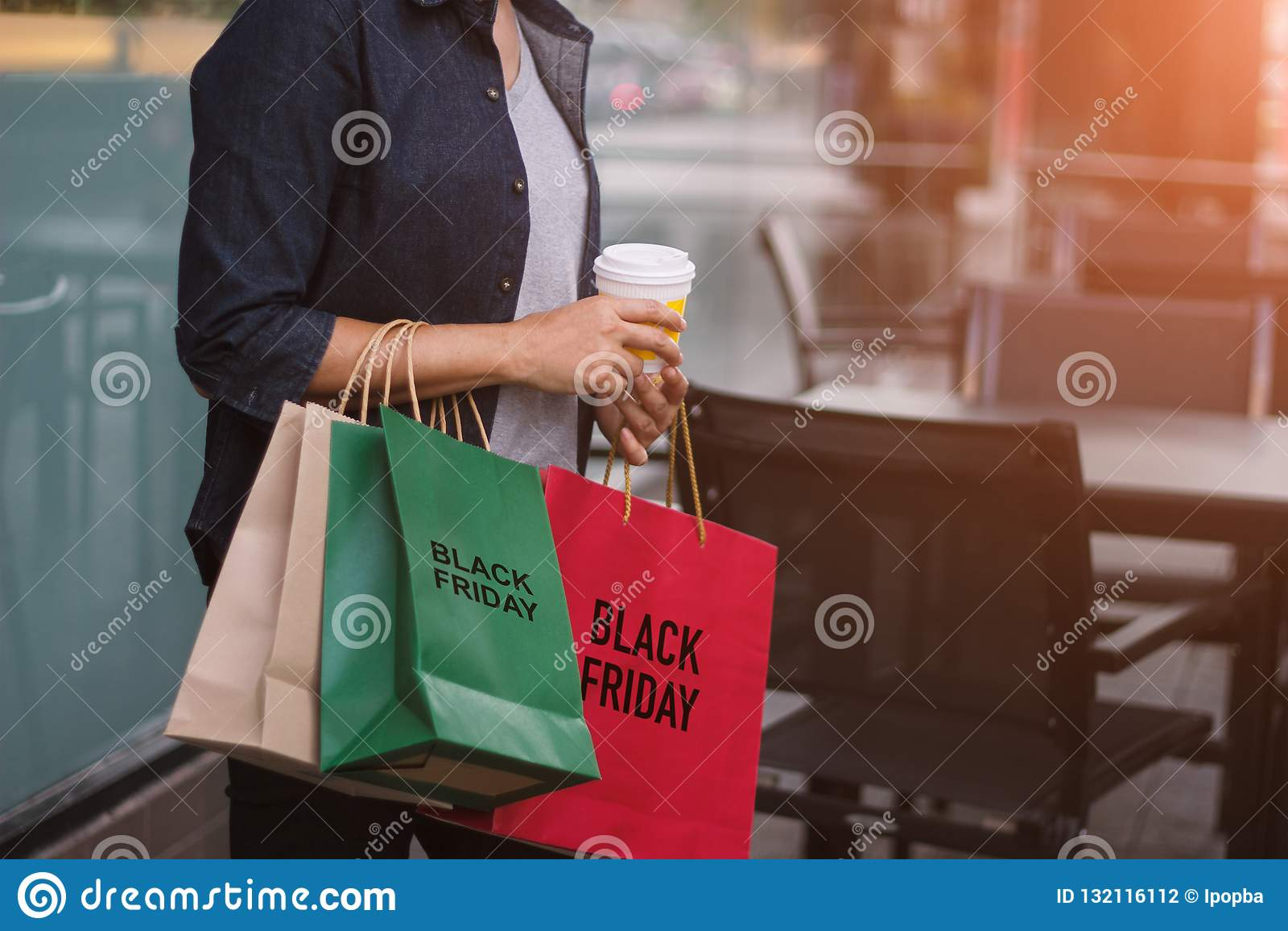 Black Friday, femme avec la tasse de café tenant des sacs à provisions