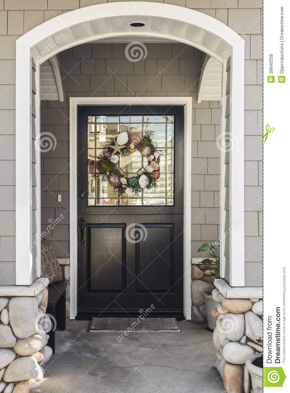 Black Front Door Of A Home Seen Through An Arch Stock