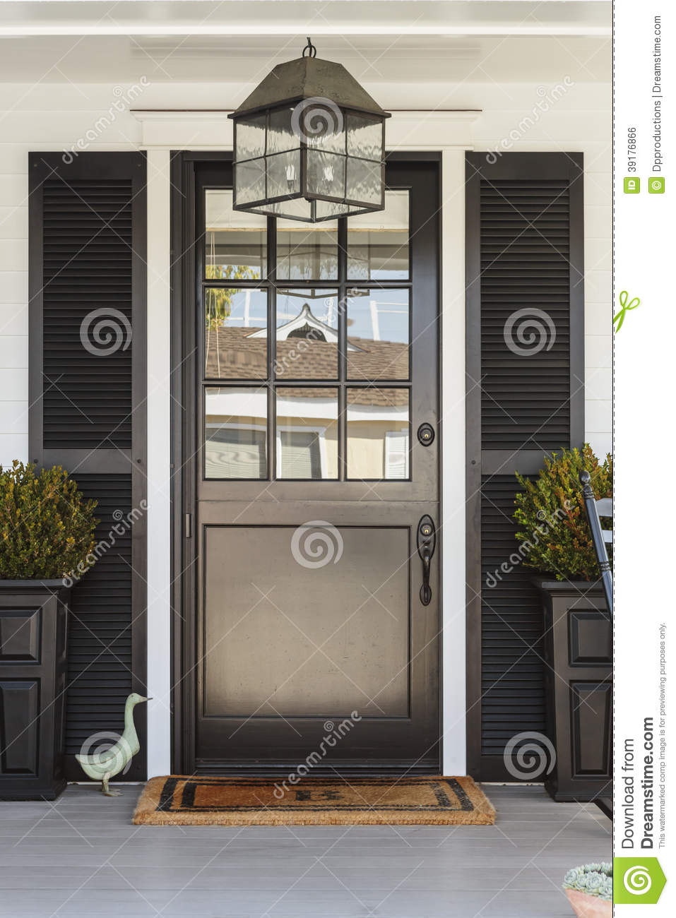 Black Front Door To A Family Home With Porch Stock Photo